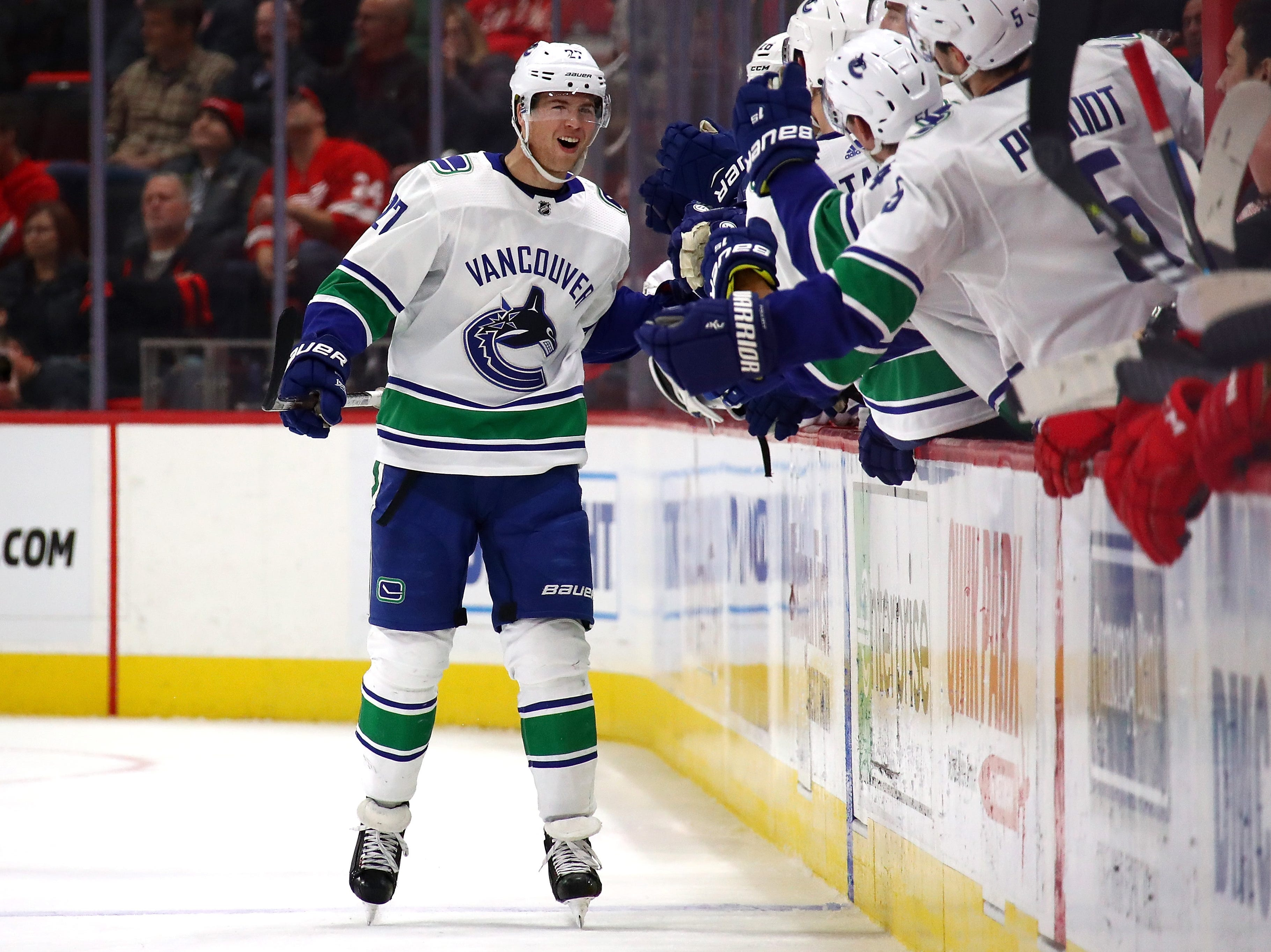 Ben Hutton (27) of the Vancouver Canucks celebrates his second period goal with teammates while playing the Detroit Red Wings at Little Caesars Arena on November 06, 2018 in Detroit, Michigan.