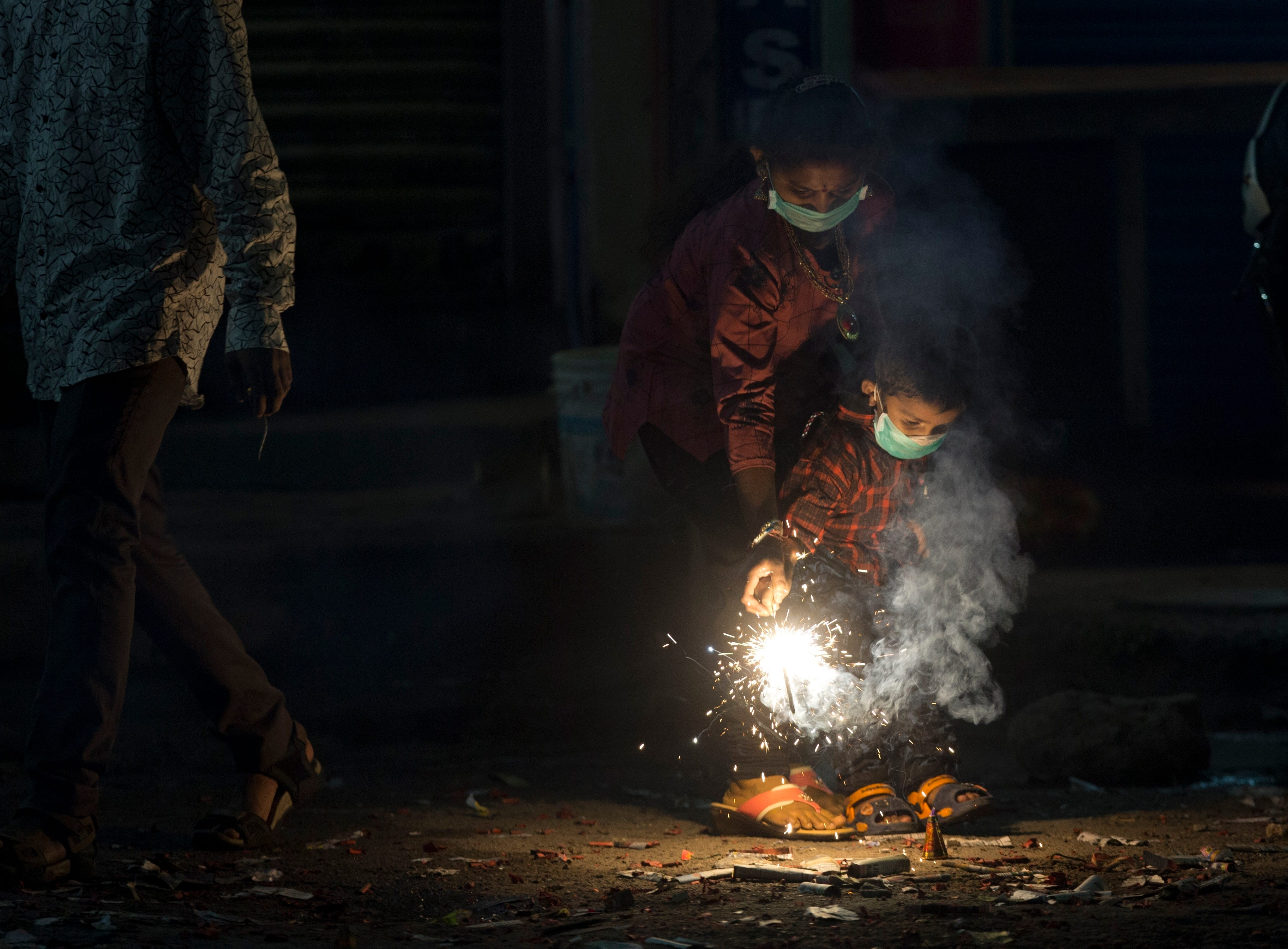 Indians light fire crackers wearing masks to fight pollution as they celebrate Diwali, the festival of lights in Hyderabad, Wednesday, Nov. 7, 2018. India's top court recently ruled that only less polluting firecrackers should be manufactured and sold.