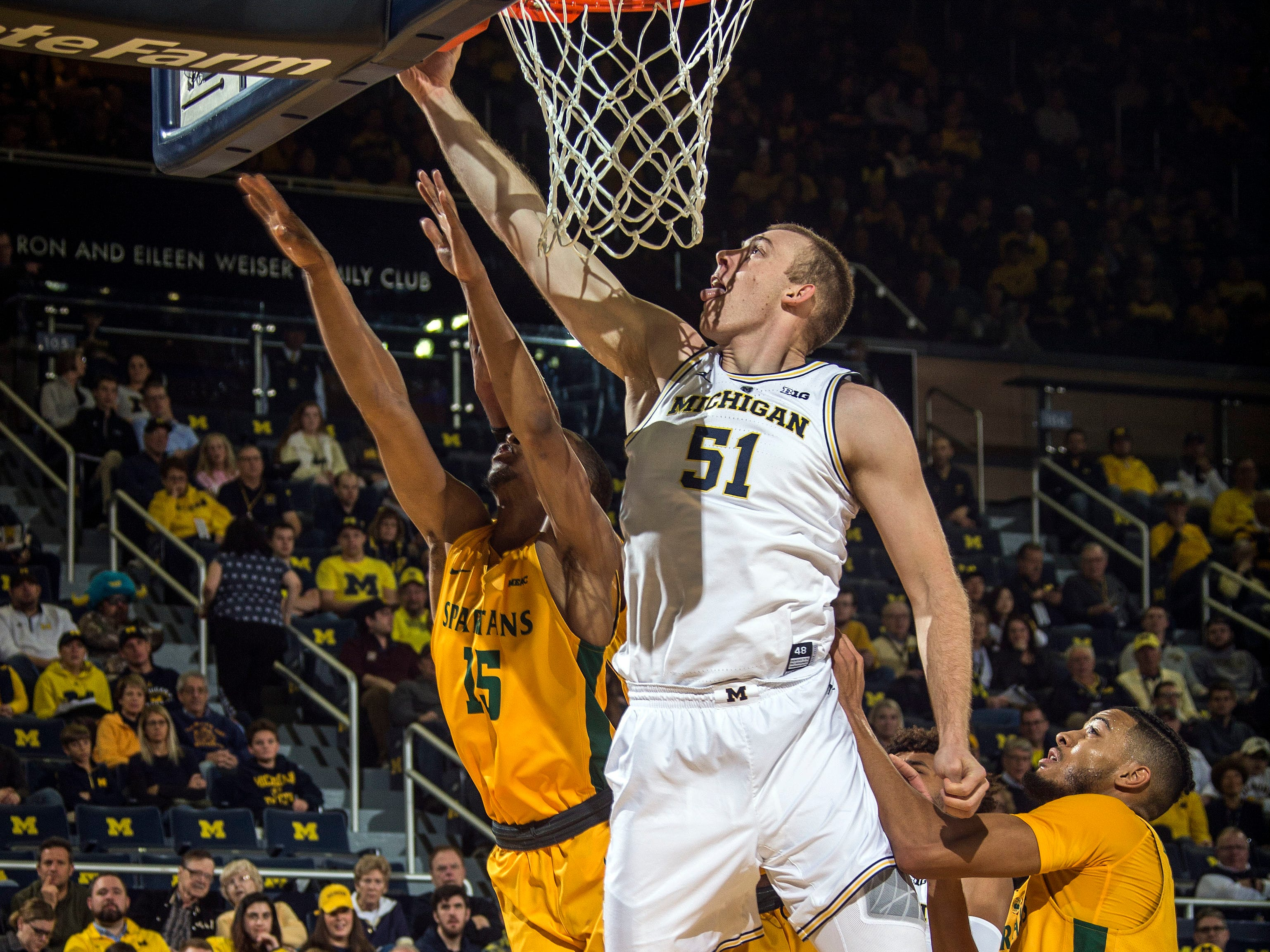 Michigan forward Austin Davis (51) goes to the basket, defended by Norfolk State guard C.J. Kelly (15) in the first half of an NCAA college basketball game at Crisler Center in Ann Arbor, Mich., Tuesday, Nov. 6, 2018.