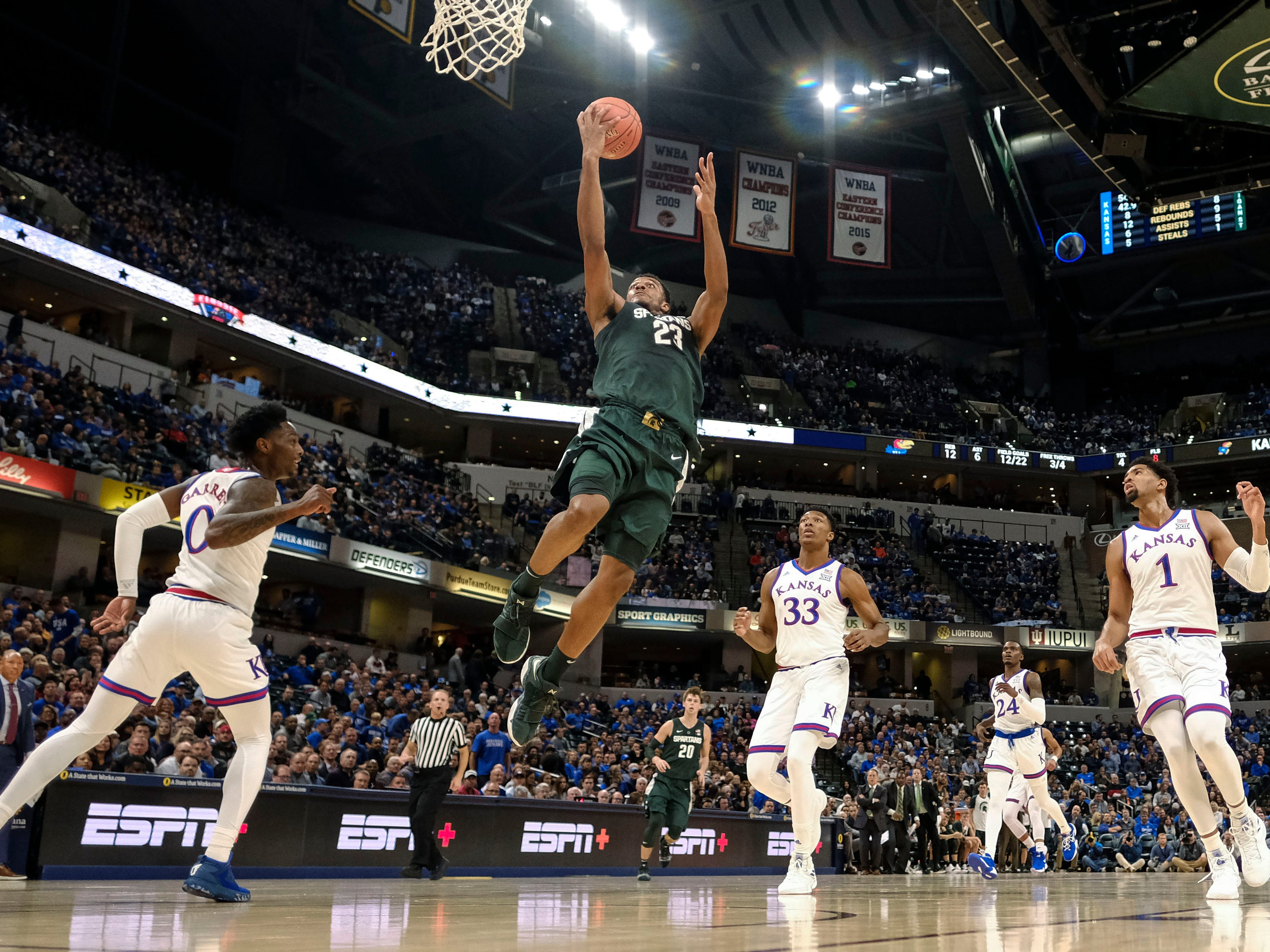 Michigan State forward Xavier Tillman (23) goes to the basket in front of Kansas defenders Marcus Garrett (0), David McCormack (33) and Dedric Lawson (1) during the first half of an NCAA college basketball game.