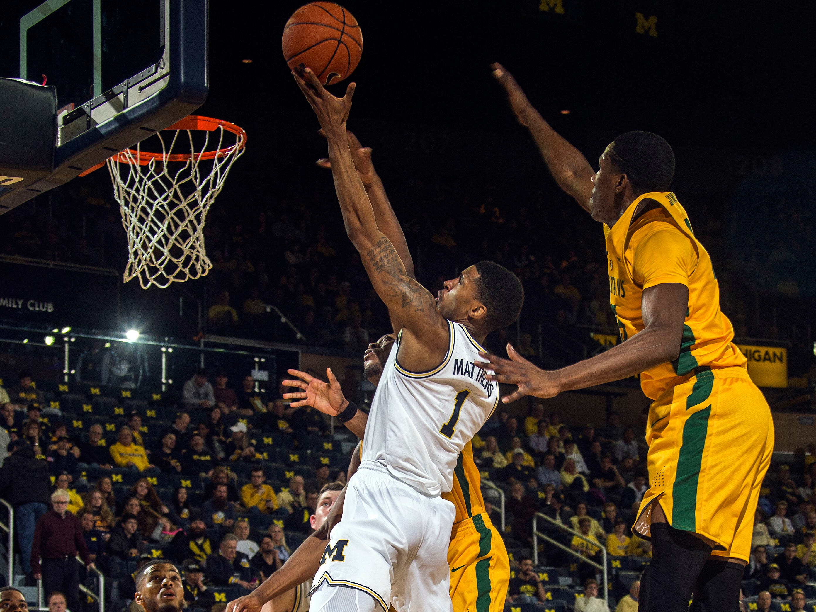 Michigan guard Charles Matthews (1) makes a layup, defended by Norfolk State guard Derrik Jamerson Jr., right, and forward Armani Branch (5) in the first half of an NCAA college basketball game at Crisler Center in Ann Arbor, Mich., Tuesday, Nov. 6, 2018.