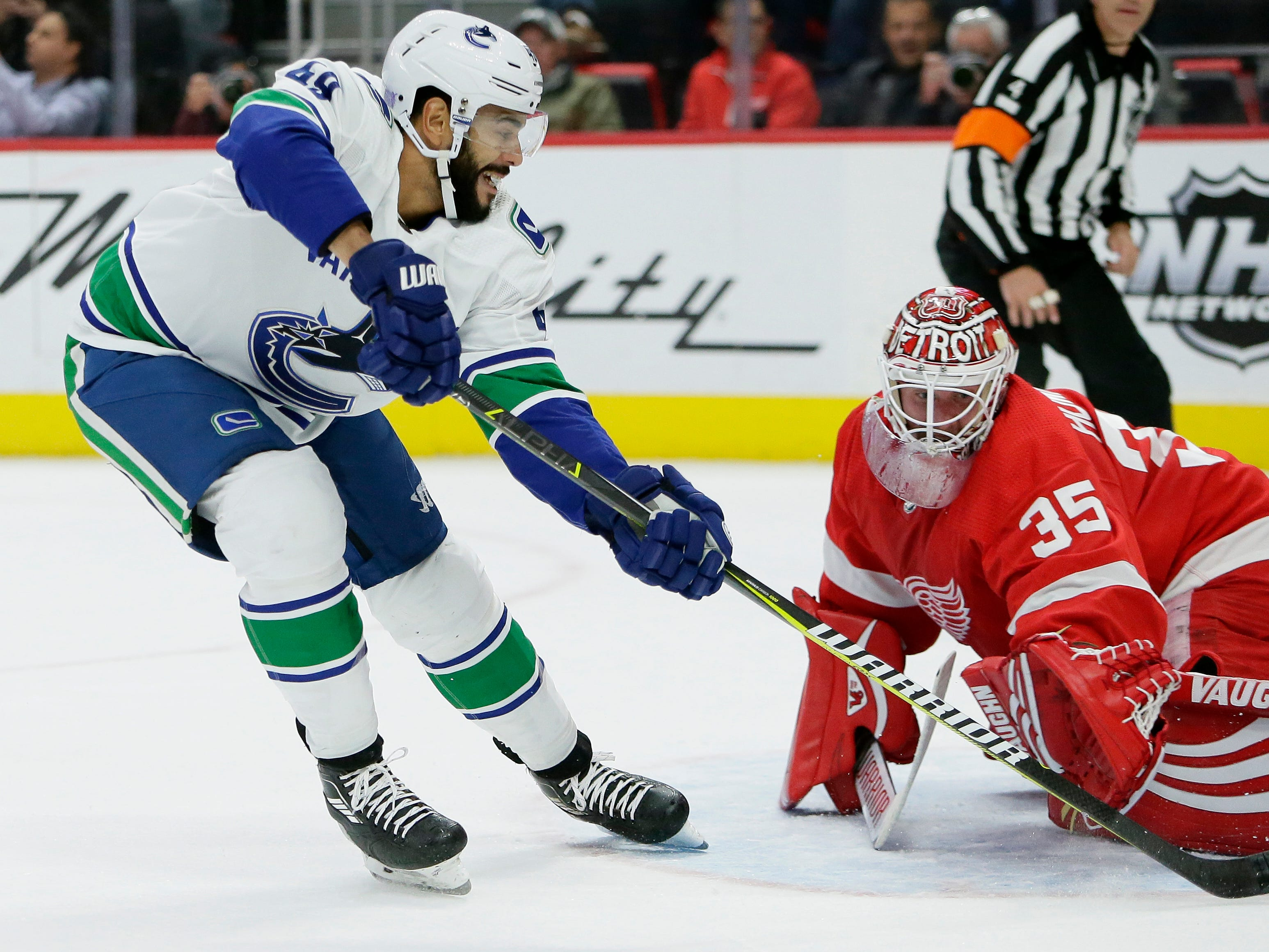 Vancouver Canucks left wing Darren Archibald (49) drives on Detroit Red Wings goaltender Jimmy Howard (35) during the first period of an NHL hockey game Tuesday, Nov. 6, 2018, in Detroit.