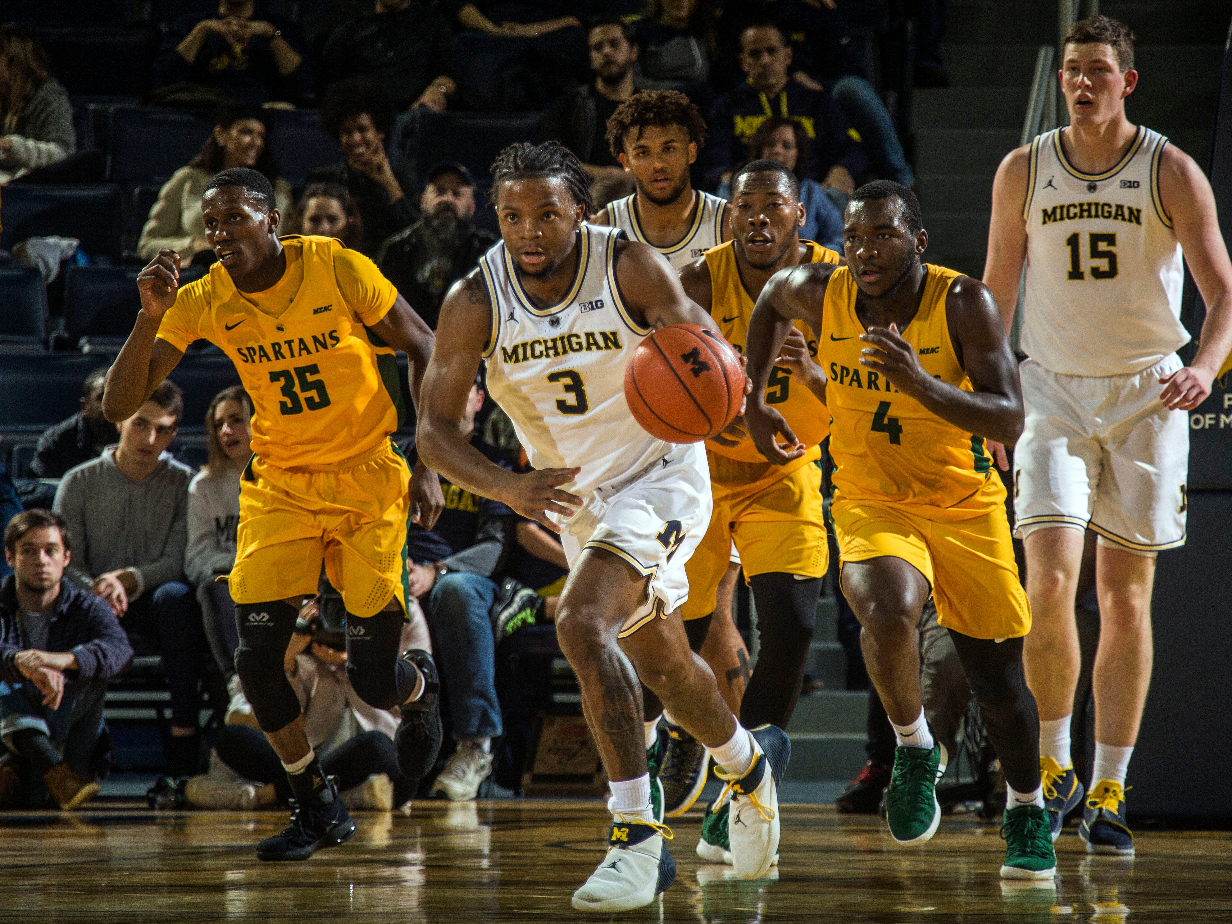 Michigan guard Zavier Simpson (3) dribbles ahead of Norfolk State guard Derrik Jamerson Jr. (35) and guard Joe Bryant Jr. (4) in the first half of an NCAA college basketball game at Crisler Center in Ann Arbor, Mich., Tuesday, Nov. 6, 2018. Michigan won 63-44.
