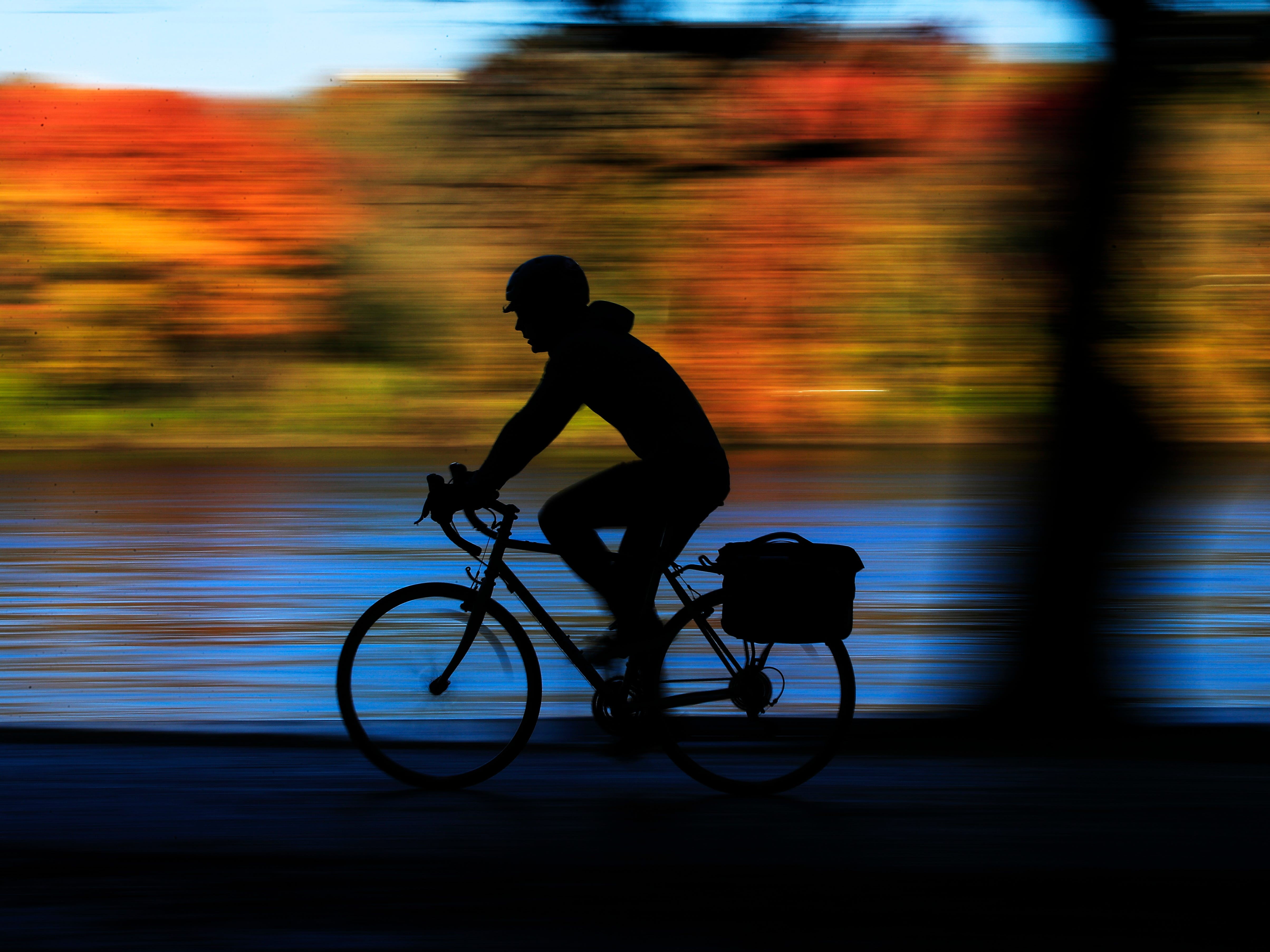 A cyclist travels along Kelly Drive on an autumn morning in Philadelphia, Wednesday, Nov. 7, 2018.