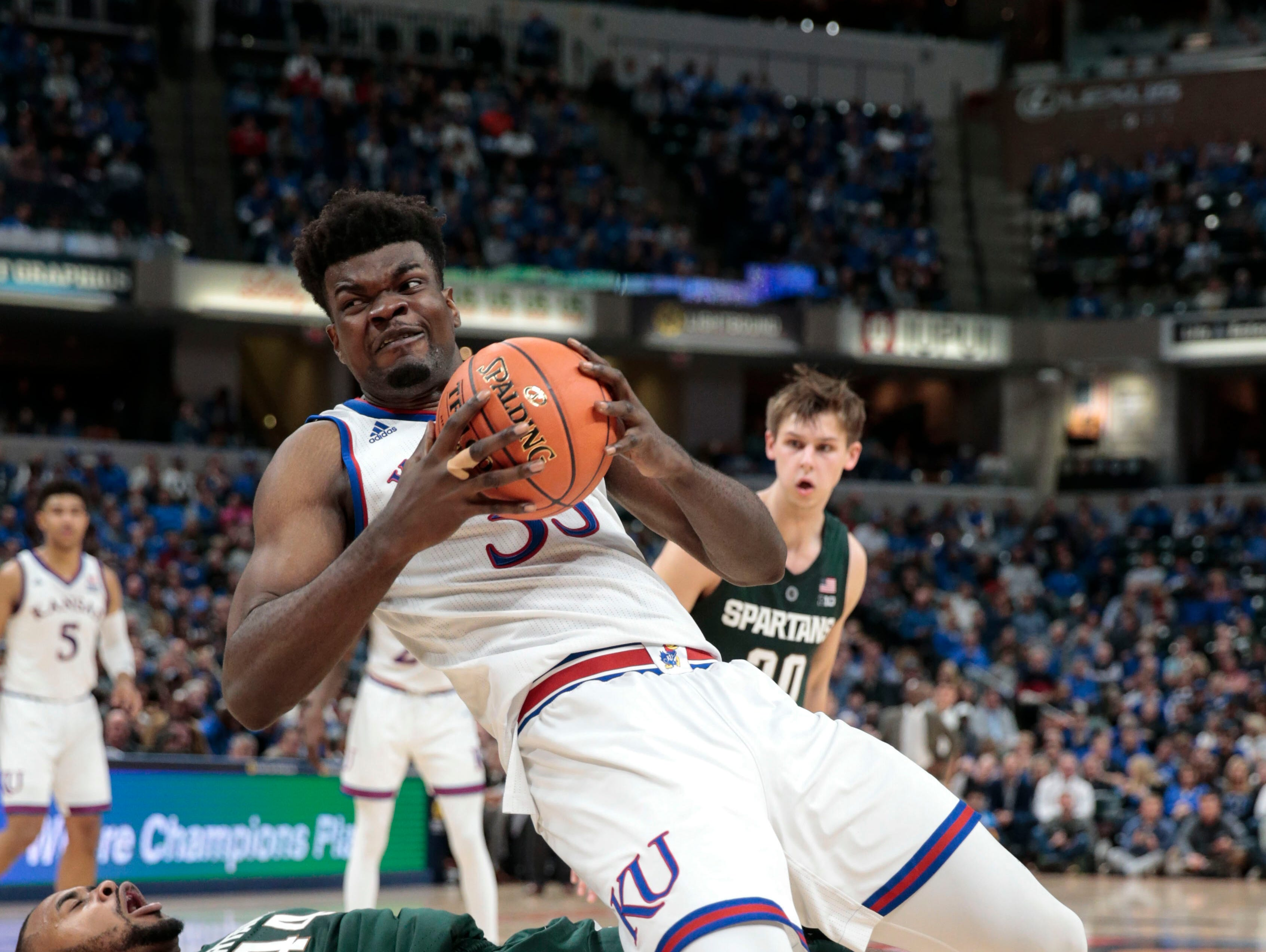 Kansas center Udoka Azubuike (35) fouls Michigan State forward Nick Ward (44) during the second half of an NCAA college basketball game at the Champions Classic in Indianapolis on Tuesday, Nov. 6, 2018. Kansas won 92-87.