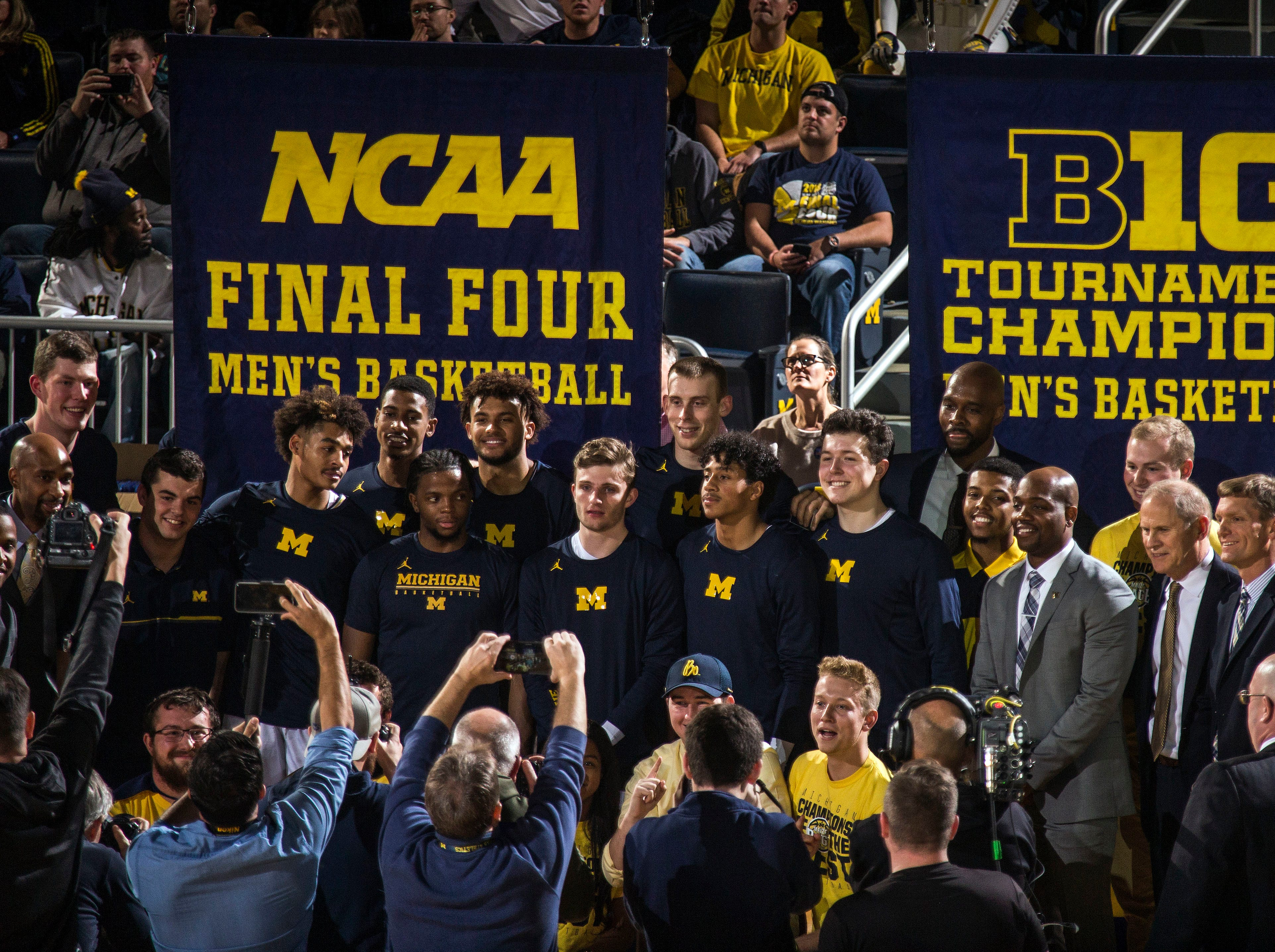 Michigan head coach John Beilein, third from right, poses for photos with his team and newly unveiled Big Ten Tournament Champions and NCAA Final Four banners, before the first half of an NCAA college basketball game against Norfolk State at Crisler Center in Ann Arbor, Mich., Tuesday, Nov. 6, 2018. (AP Photo/Tony Ding)