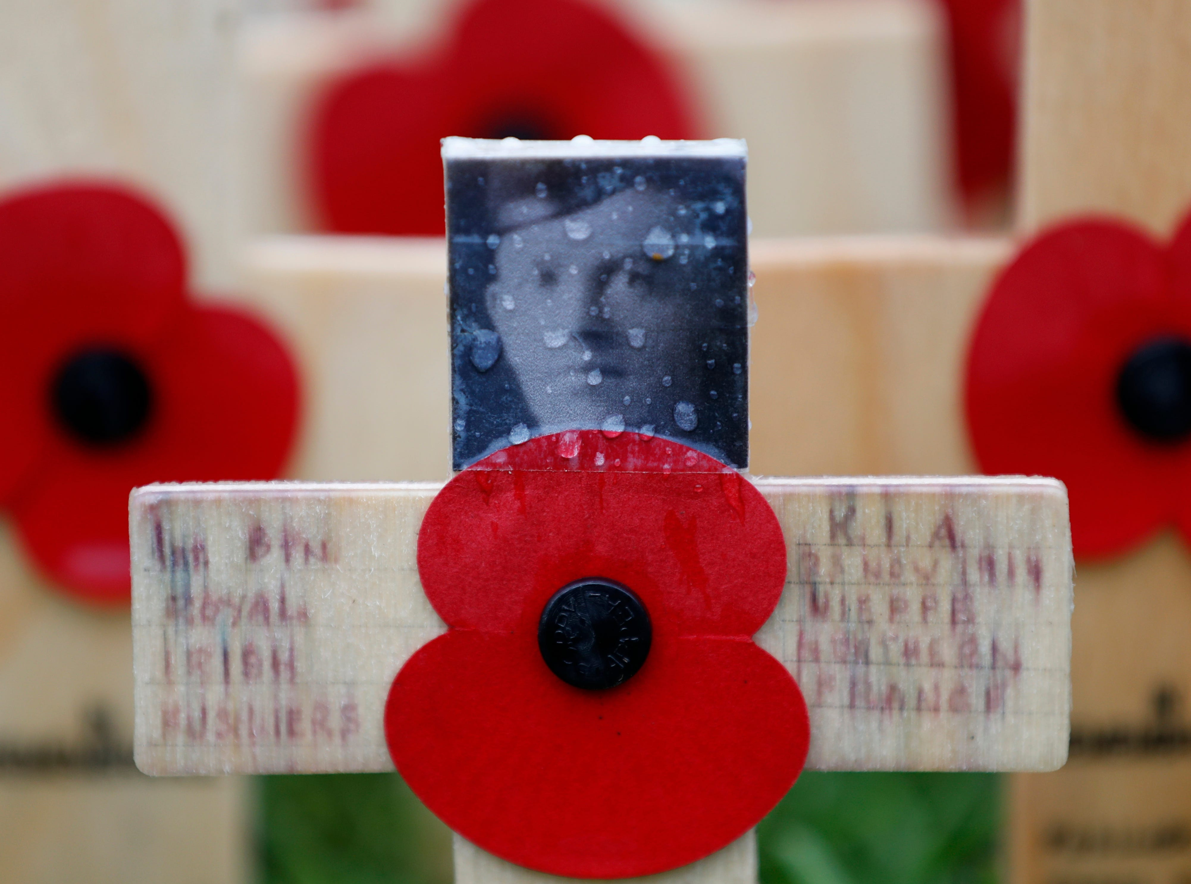 A rain drop covers a photograph of Gerald Briedell of the Royal Irish Regiment, which adorns a cross placed in the Field of Remembrance at Westminster Abbey in preparation for the annual Armistice Day on Nov. 11, in London, Wednesday, Nov. 7, 2018.