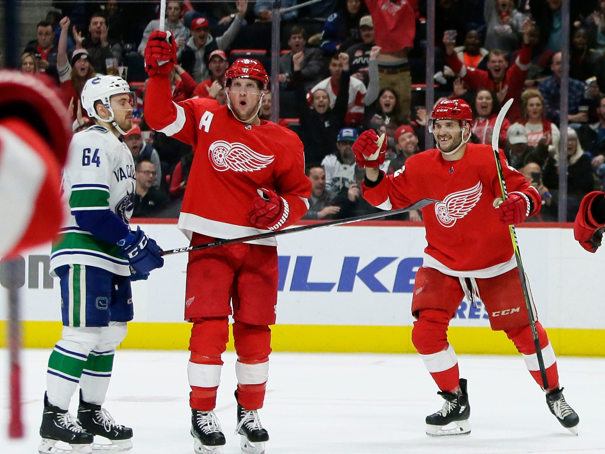 Detroit Red Wings left wing Justin Abdelkader (8) celebrates his second period goal with right wing Martin Frk (42), of the Czech Republic, as Vancouver Canucks center Tyler Motte (64) skates off during the second period of an NHL hockey game.