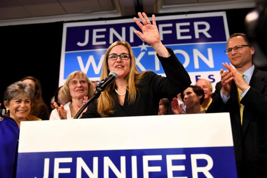 Democrat Jennifer Wexton talks to supporters, flanked by her mother, Paula Tosini and husband, Andrew, after she beat incumbent Barbara Comstock in Virginia's 10th congressional district, in Dulles, Va.