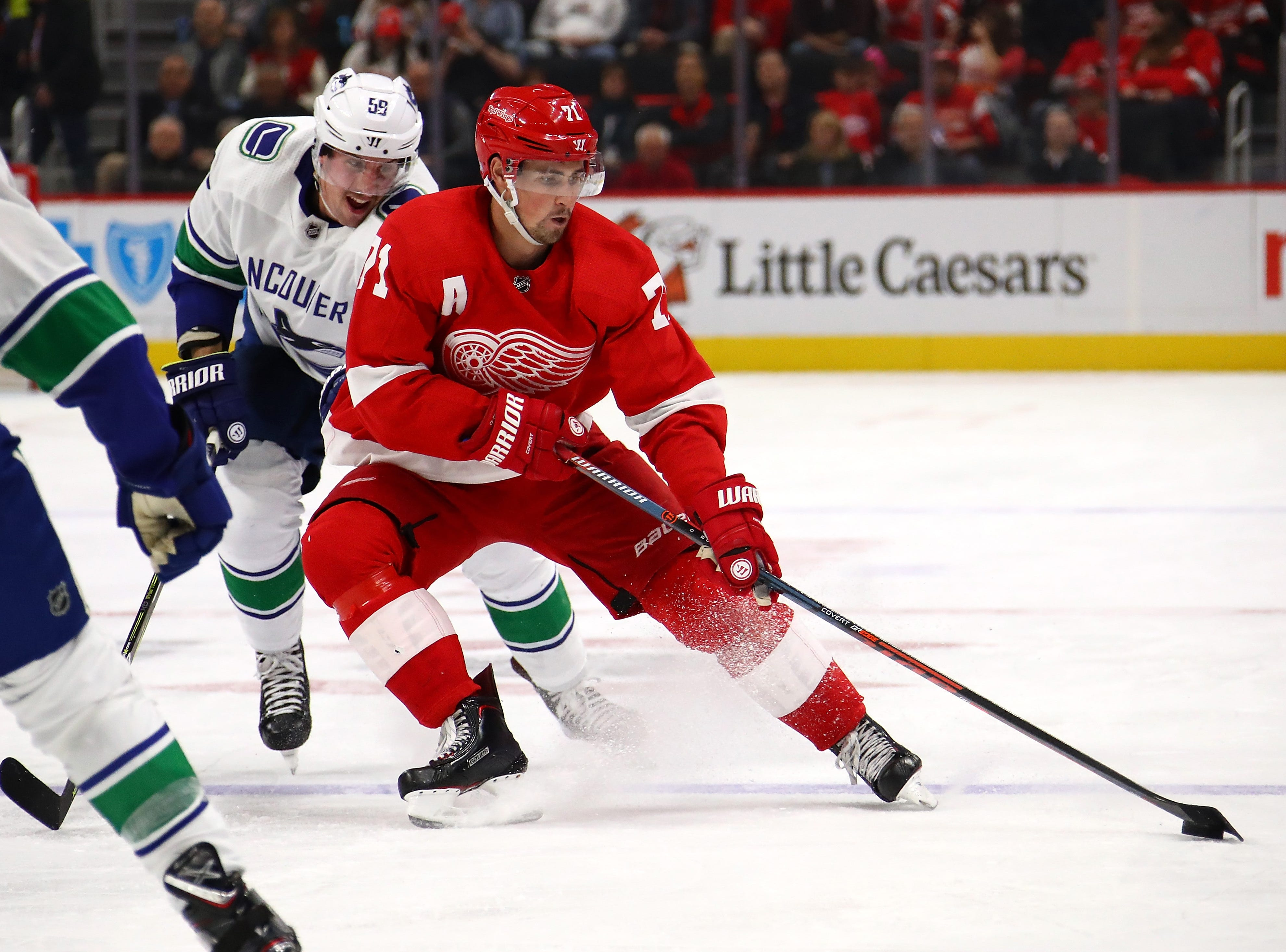 Dylan Larkin (71) of the Detroit Red Wings tries to control the puck in front of Tim Schaller (59) of the Vancouver Canucks during the second period at Little Caesars Arena on November 06, 2018 in Detroit, Michigan.