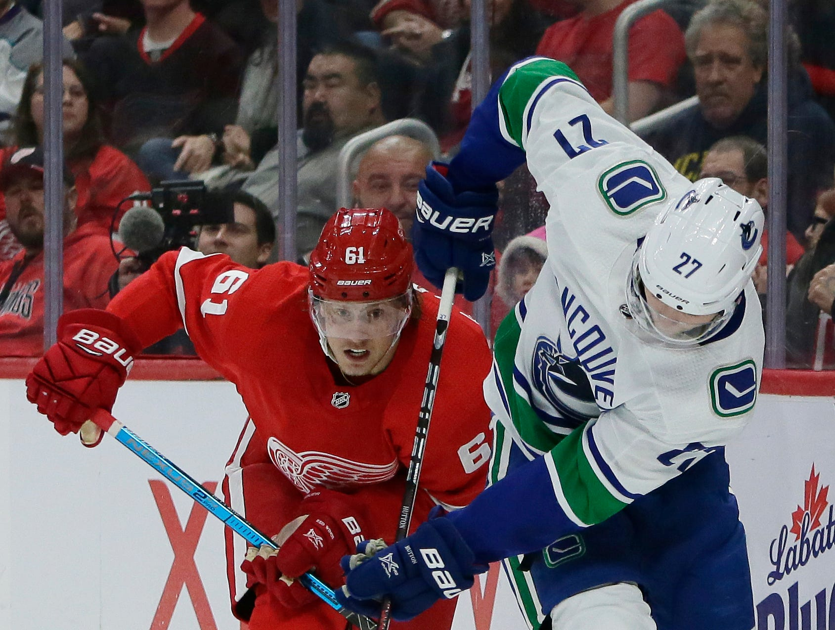 Vancouver Canucks defenseman Ben Hutton (27) is pursued by Detroit Red Wings left wings Jacob de la Rose (61), of Sweden, behind the net during the second period of an NHL hockey game Tuesday, Nov. 6, 2018, in Detroit.