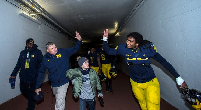 Michigan defensive coordinator Don Brown gives a high-five to linebacker Devin Gil in the Michigan Stadium tunnel after the win over Penn State.
