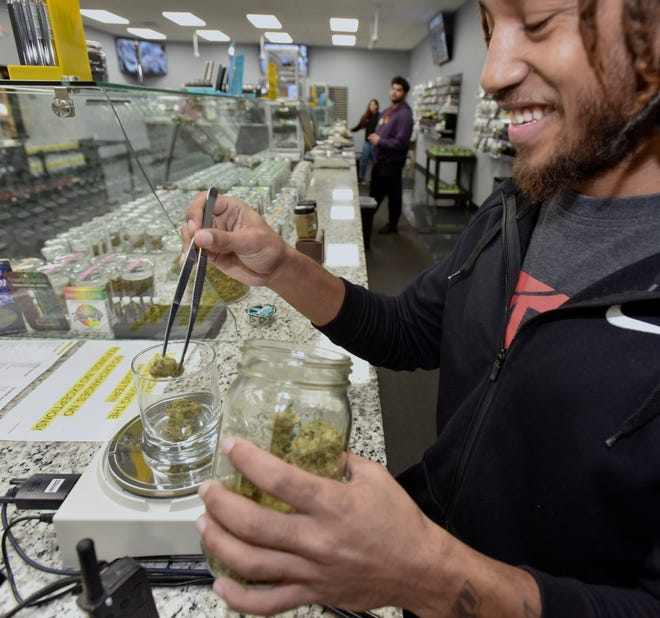 """Bud tender"" Delvante Perry of Canton Township weighs out an 1/8th ounce of Blue Zkittles for a patient Wednesday at Far West Holistic Center in Detroit."