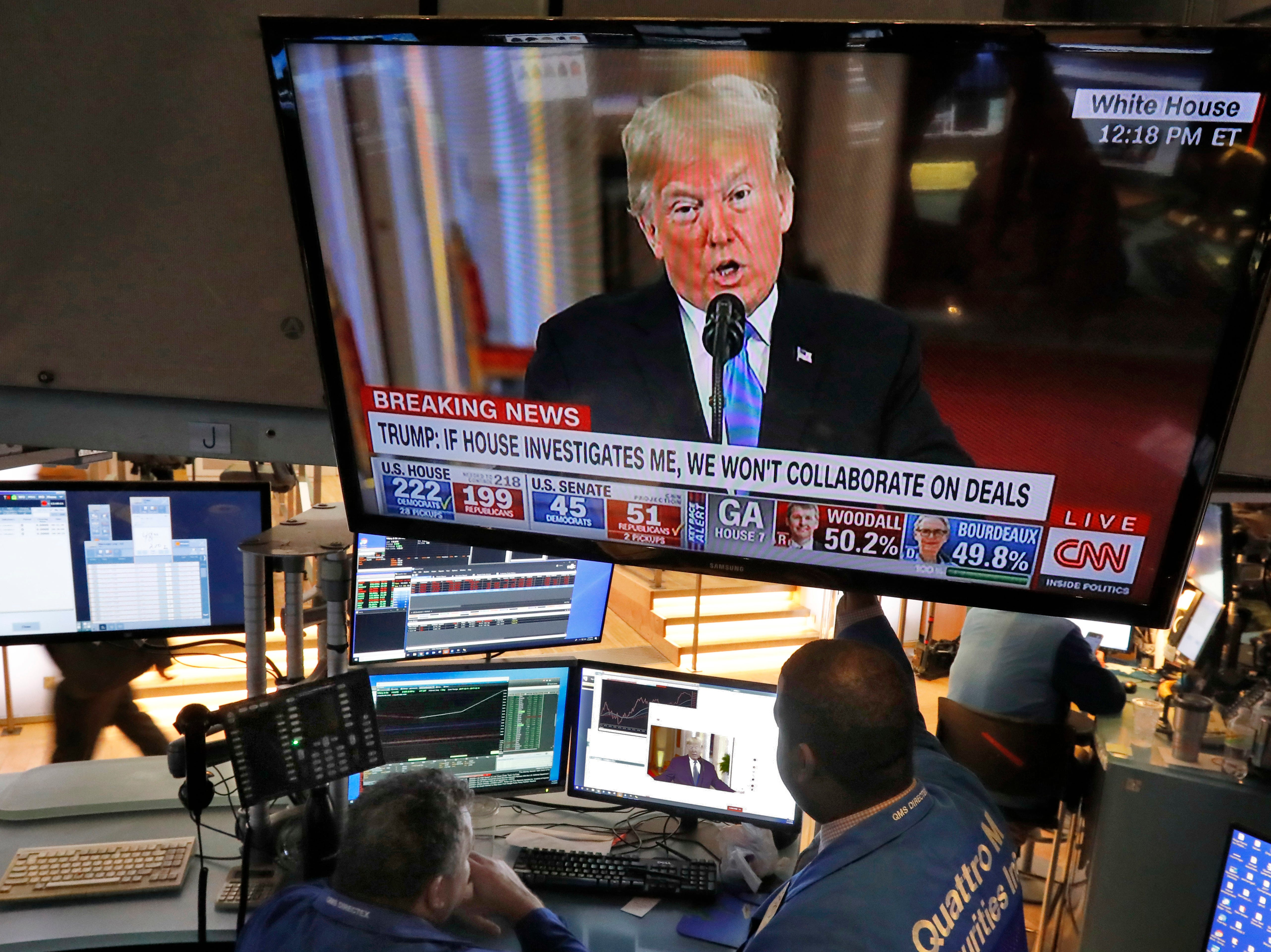 Traders on the floor of the New York Stock Exchange watch President Donald Trump's news conference, Wednesday, Nov. 7, 2018. Technology and health care stocks are leading indexes broadly higher on Wall Street as results of the midterm elections came in largely as investors had expected.