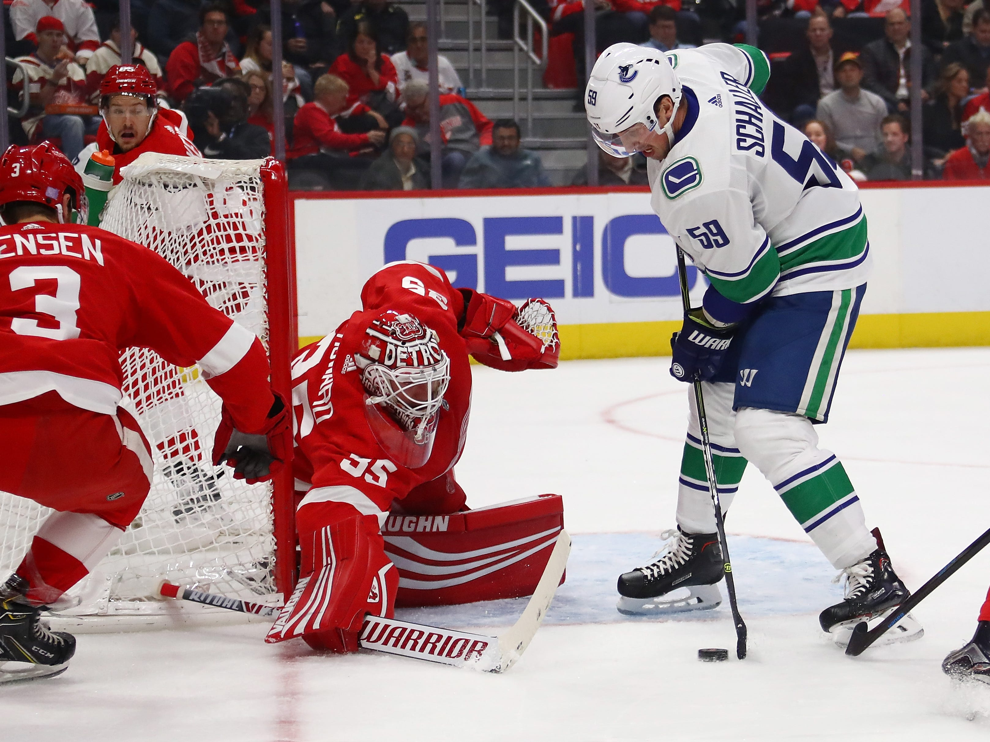Jimmy Howard (35) of the Detroit Red Wings makes a first period save on Tim Schaller (59) of the Vancouver Canucks at Little Caesars Arena.