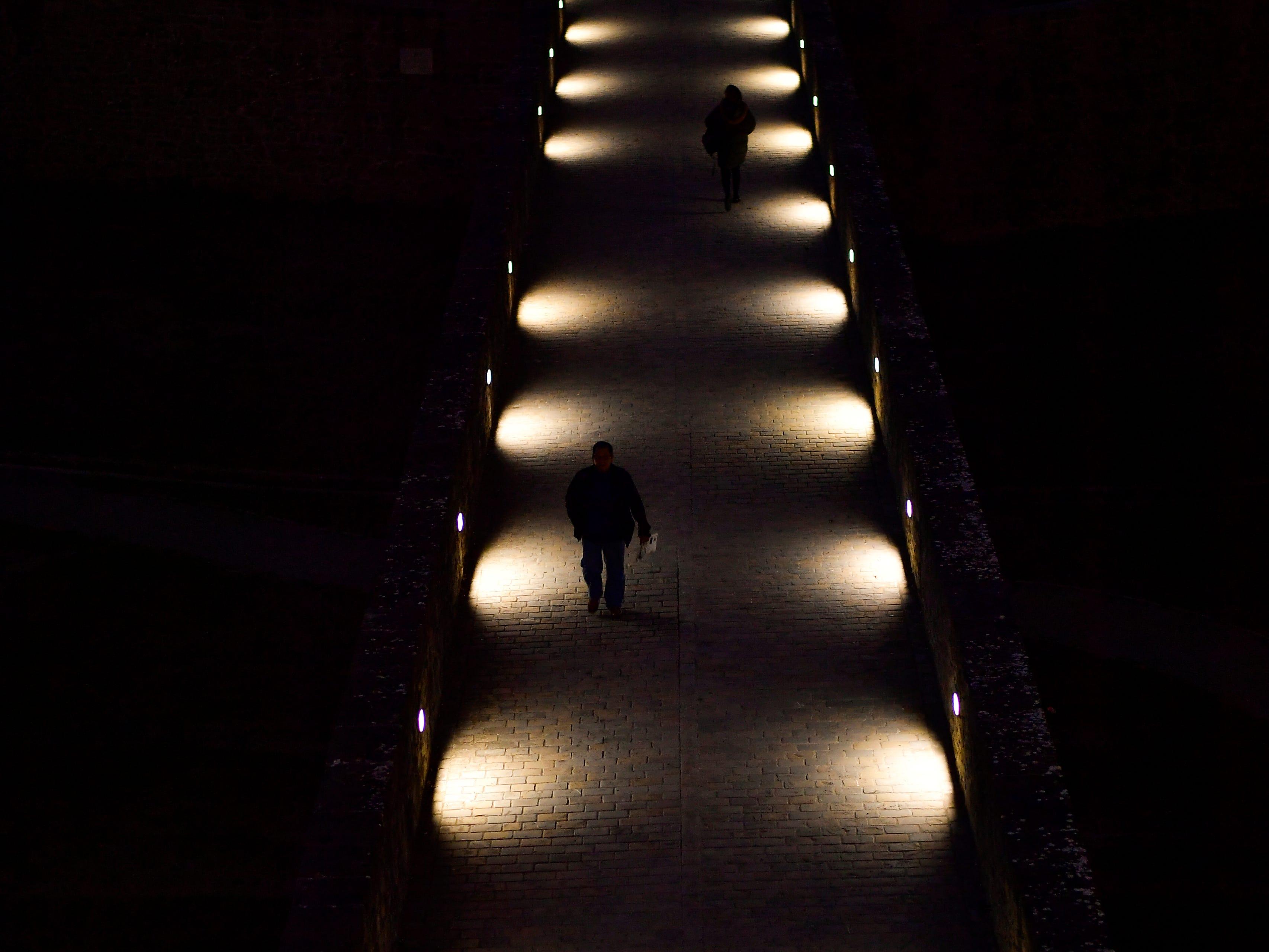People walk on a bridge in Pamplona, northern Spain, Wednesday, Nov. 7, 2018.