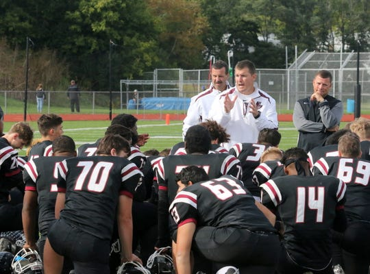 Elmira head coach Jimmy McCauley talks to his players after a 30-8 victory over Syracuse Corcoran on Sept. 22, 2018 at Ernie Davis Academy. Elmira assistants Jeff Edwards, left, and Mike Johnston Jr. are behind McCauley.