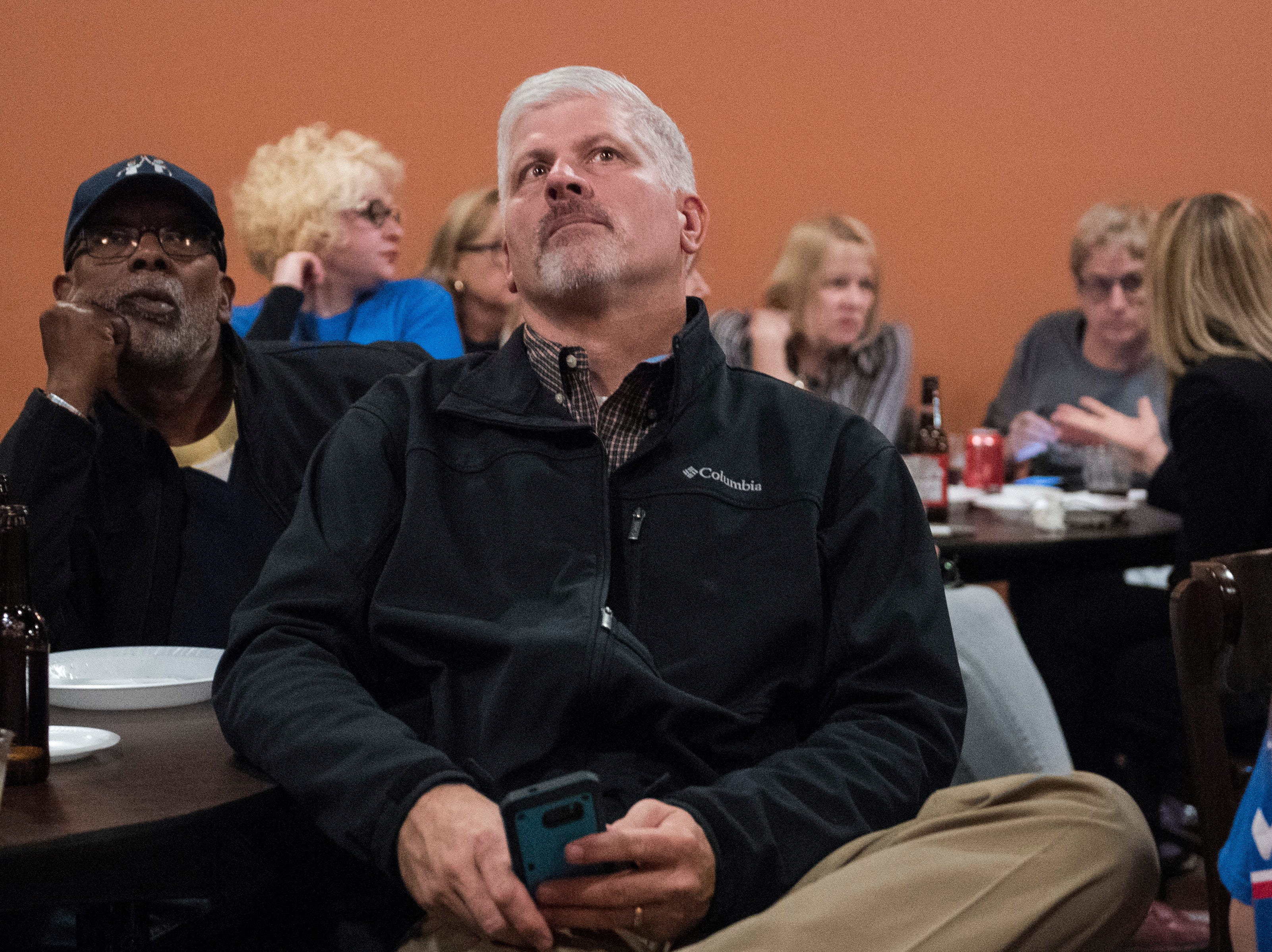 Darrell McKnight, left, and Eric Williams stare up at the tv while the 2018 election results come in during the  Vanderburgh County Democratic watch party held at DiLegge's Restaurant Tuesday Nov. 6, 2018.