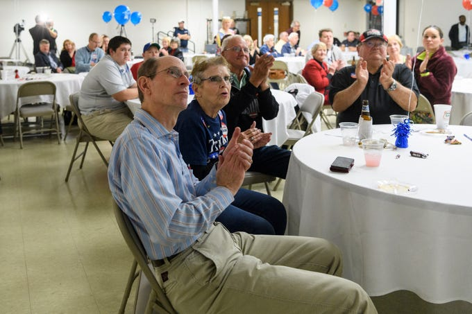 J.D. Strouth, front, and Brenda Bergwitz, sitting directly beside him, and nearly 75 other people watch newly elected U.S. Senator Mike Braun, not pictured, give a speech on the television during the republican watch party at C K Newsome Community Center in Evansville, Ind., Tuesday, Nov. 6, 2018.
