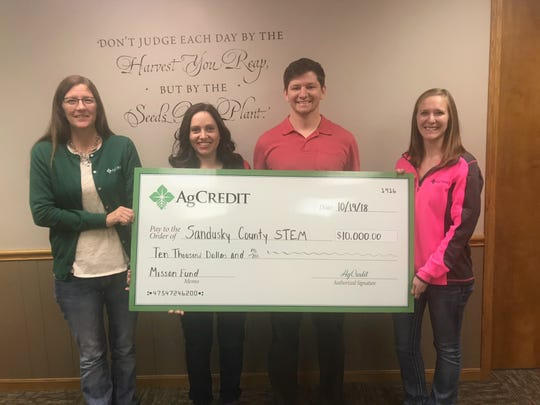 Ruthann Buhrow and Erica Bloomer of the AgCredit Fremont team presented a check to Doug Steinberger and Elizabeth Royster of Sandusky County STEM.