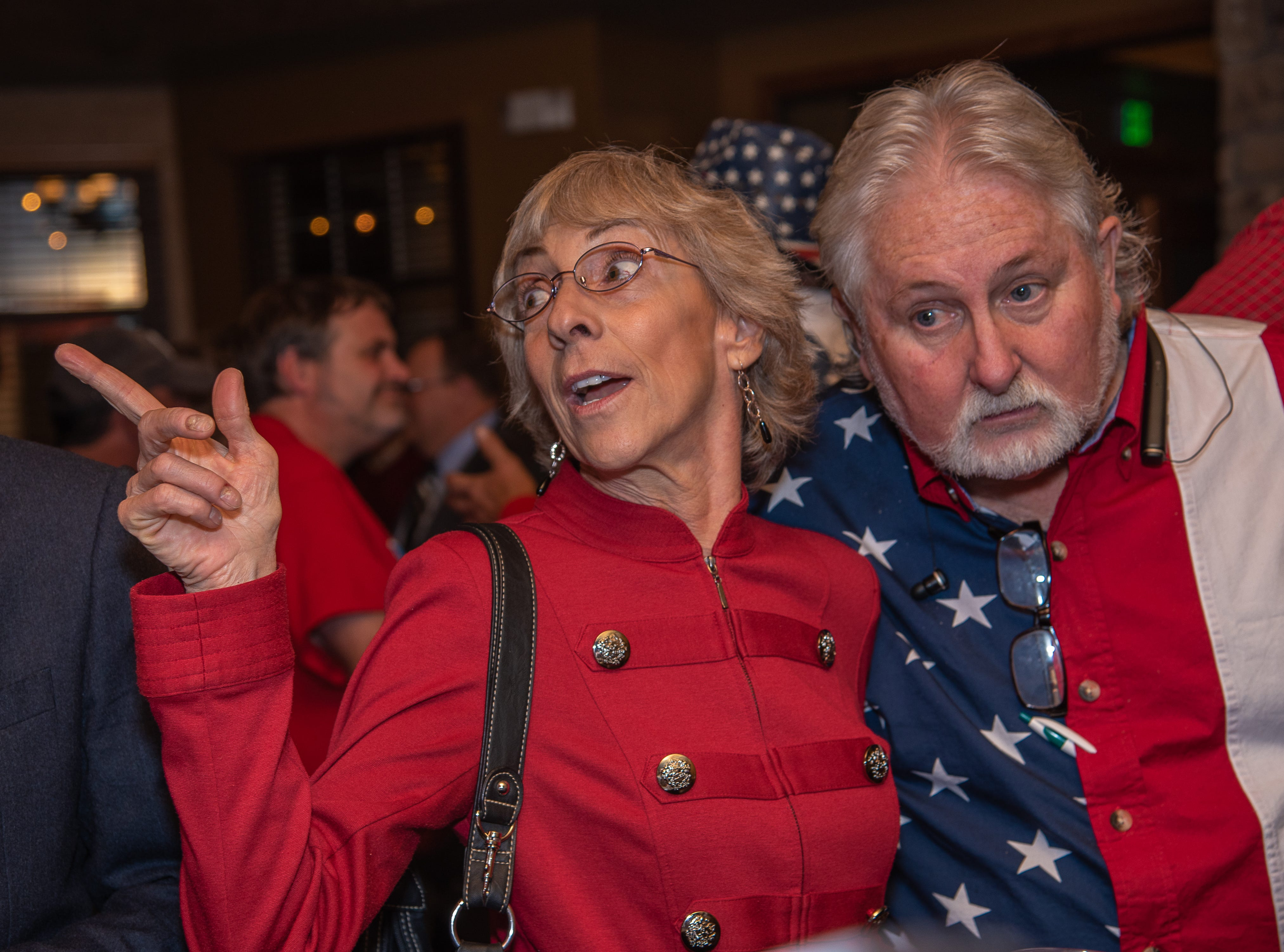 GOP House District 52 candidate Donna Walter points to election results on a screen as she hugs supporter Steve Faler at an election watch party on Tuesday, November 6, 2018, at Ptarmigan Country Club in Fort Collins, Colo.