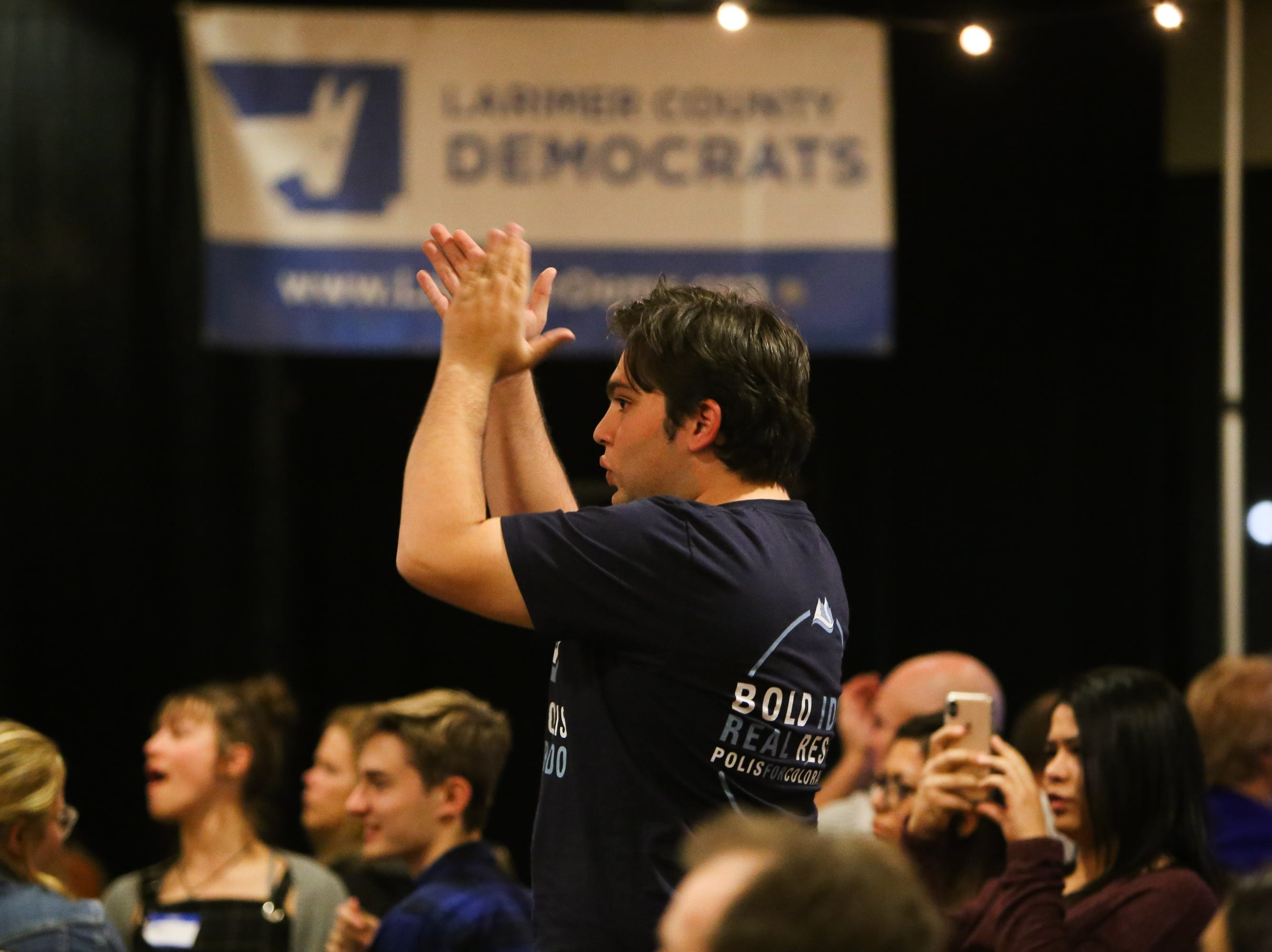 Thelanious Rider stands up and cheers during during the Democratic watch party at the Fort Collins Marriott .