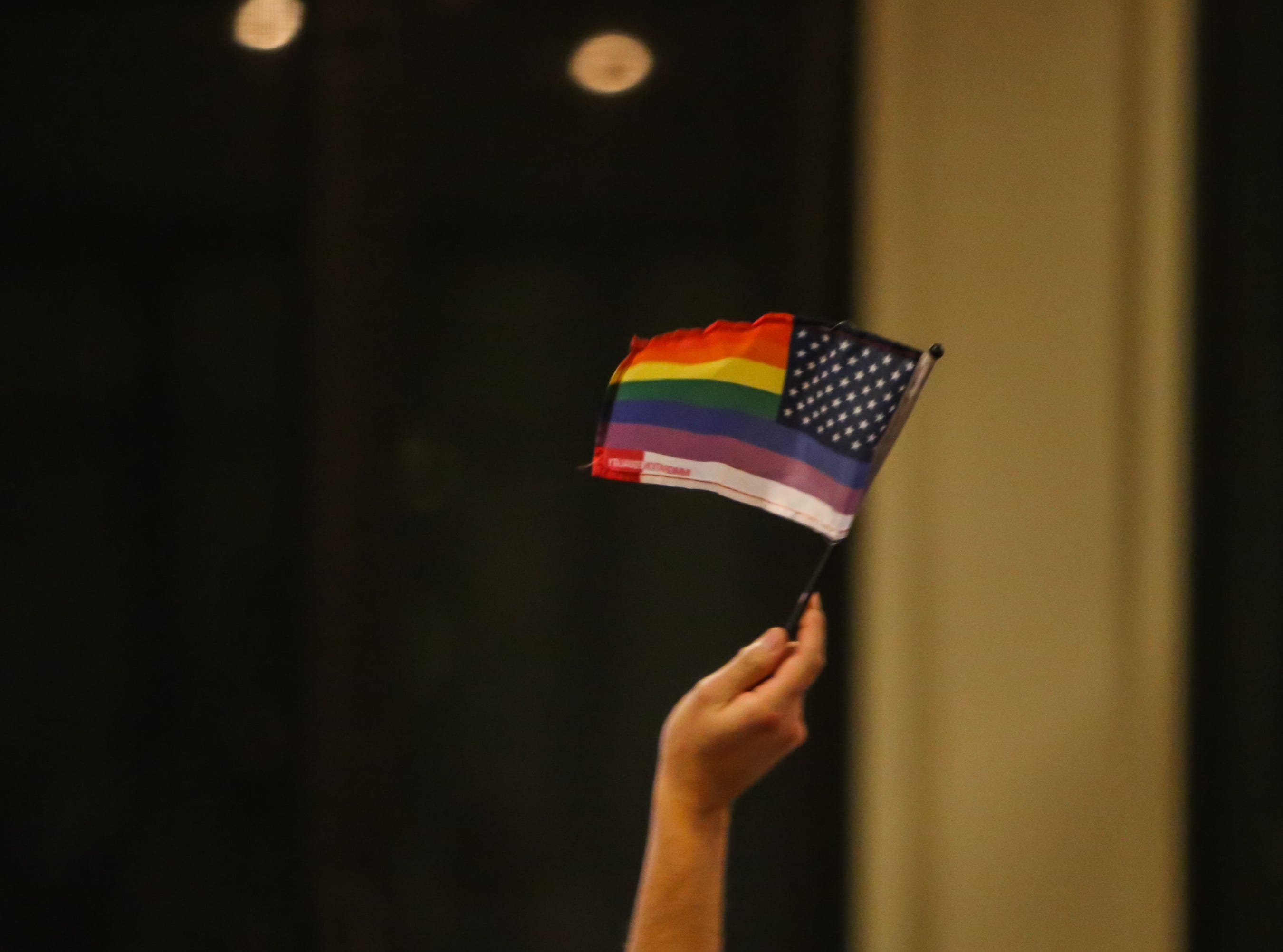 A Pride flag in the style of the American flag is waved at the Larimer County Democrats' watch party Tuesday at the Fort Collins Marriott. The flag was waved anytime Jared Polis was mentioned. Polis was named the first openly gay governor.