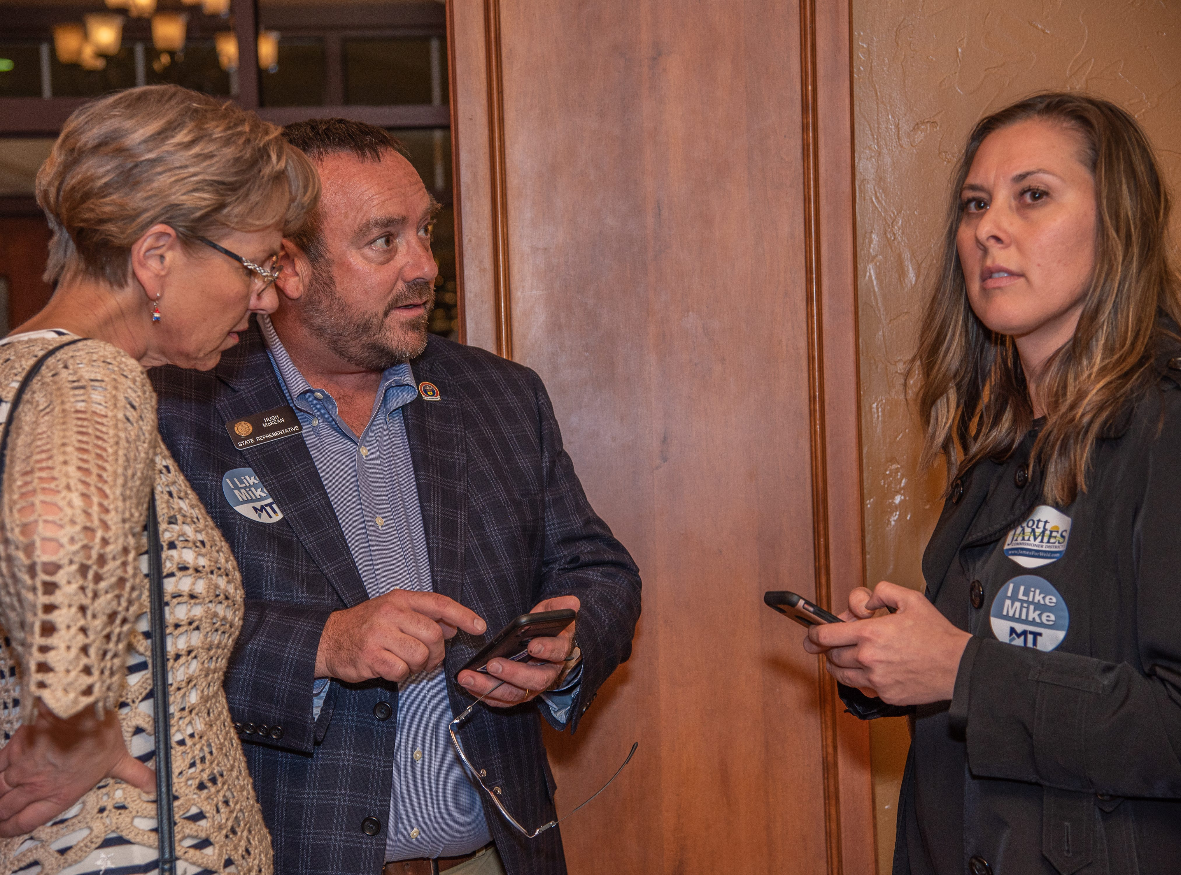 State Rep. Hugh McKean reacts to election results with his wife Kristin McKean and Amy Parks, campaign manager, at a watch party on Tuesday, November 6, 2018, at Ptarmigan Country Club in Fort Collins, Colo.