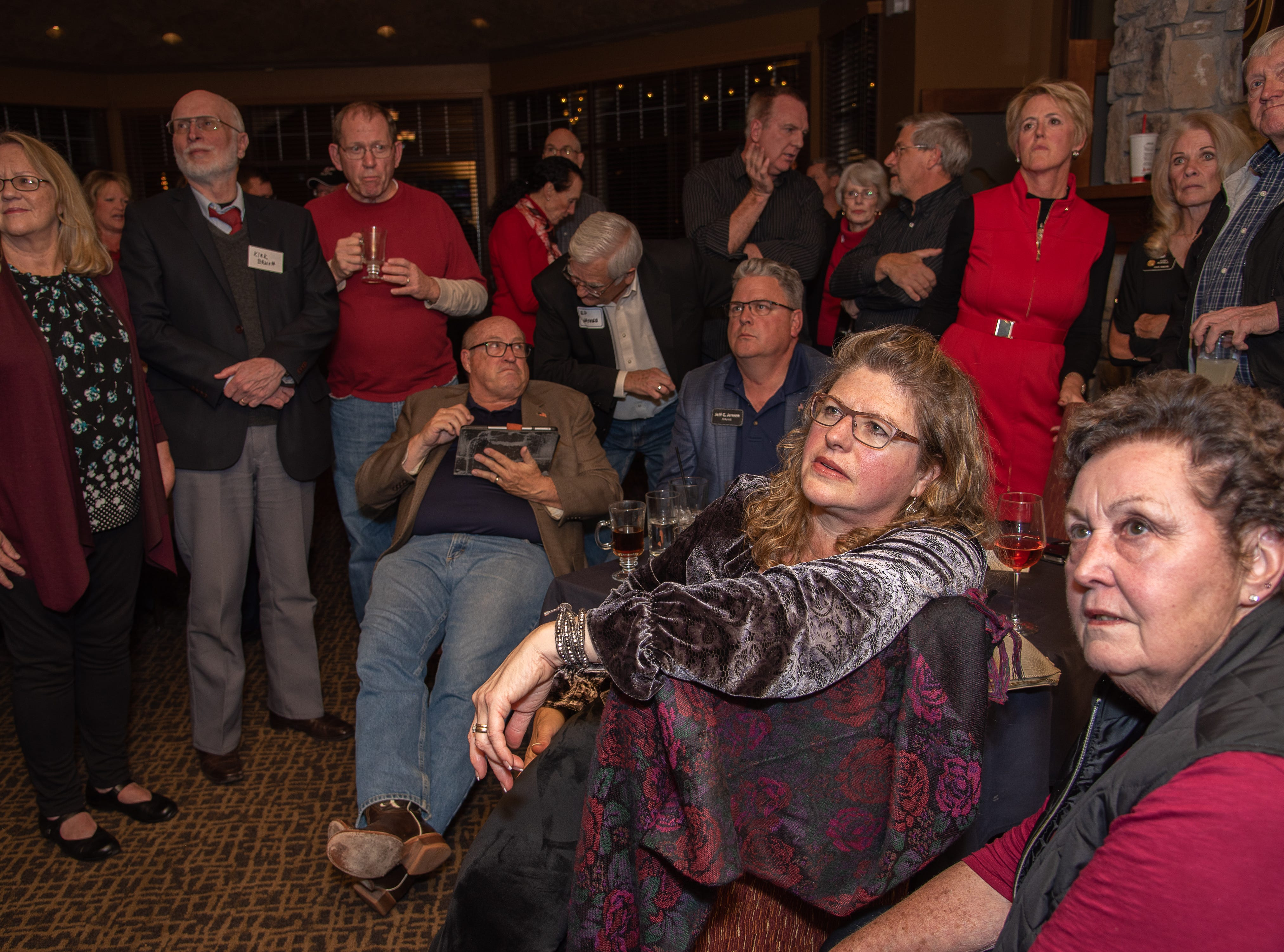Aimee Jensen and Myrna Rodenberger, front, react to early election results with fellow GOP supporters on Tuesday, November 6, 2018, at Ptarmigan Country Club in Fort Collins, Colo.
