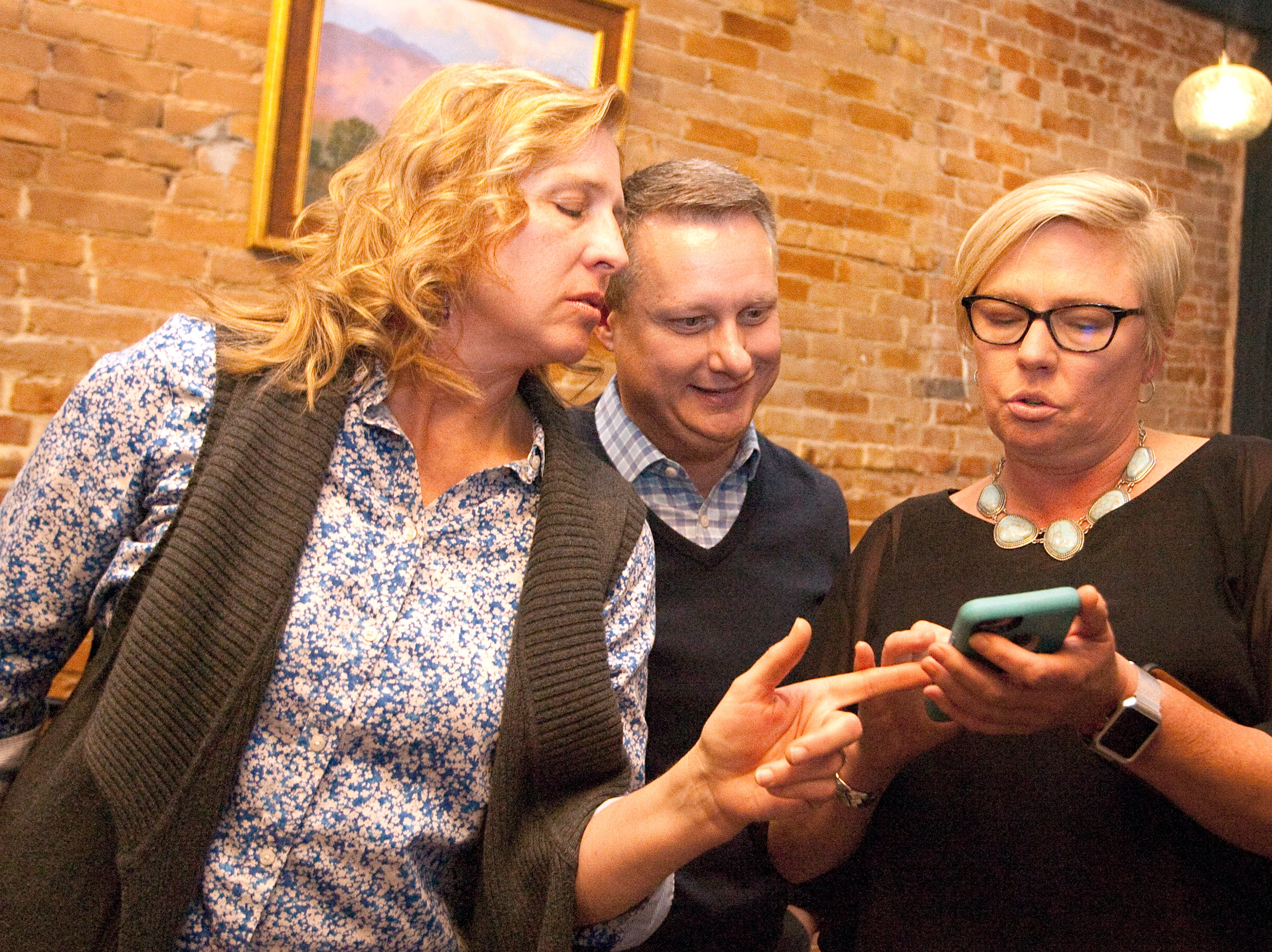 From left, Jody Shadduck ­McNally, campaign treasurer; Michael Allen, CEO for SummittStone Health Partners; and Natalie Diekmann, marketing and communication director for 1A, keep a close on Diekmann's phone while waiting for results during a watch party held at the Loveland TapHouse Tuesday evening.