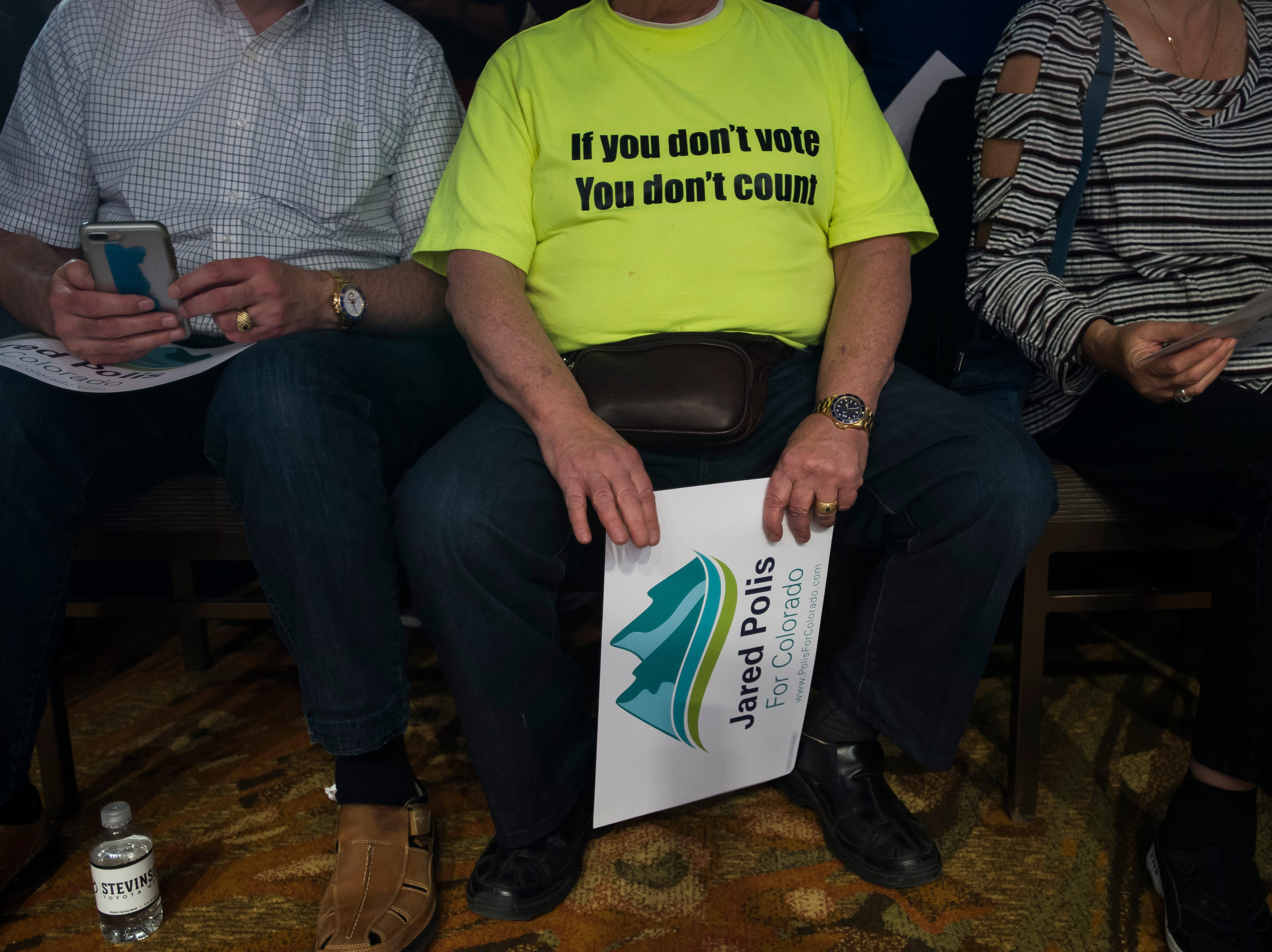 Golden, Colo., resident John Crisci holds a Jared Polis sign while sitting in the front row at Democratic candidate for Colorado governor Jared Polis's election watch party on Tuesday, Nov. 6, 2018, at the Westin Denver Downtown hotel in Denver, Colo.