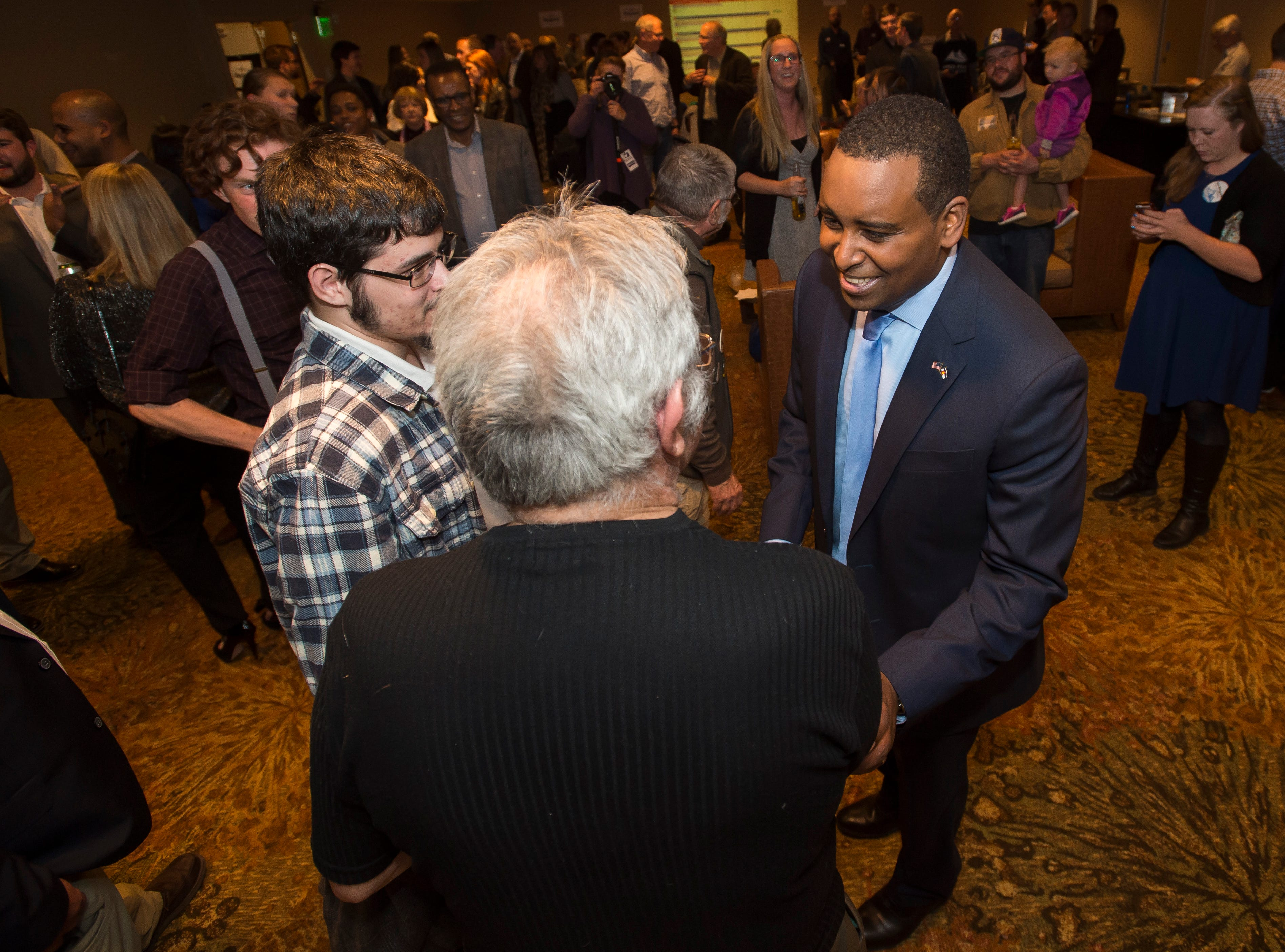 Colorado 2nd congressional district candidate Joe Neguse greets father and son Tim and Daniel Goult during his election watch party on Tuesday, Nov. 6, 2018, at the Westin Denver Downtown hotel in Denver, Colo.