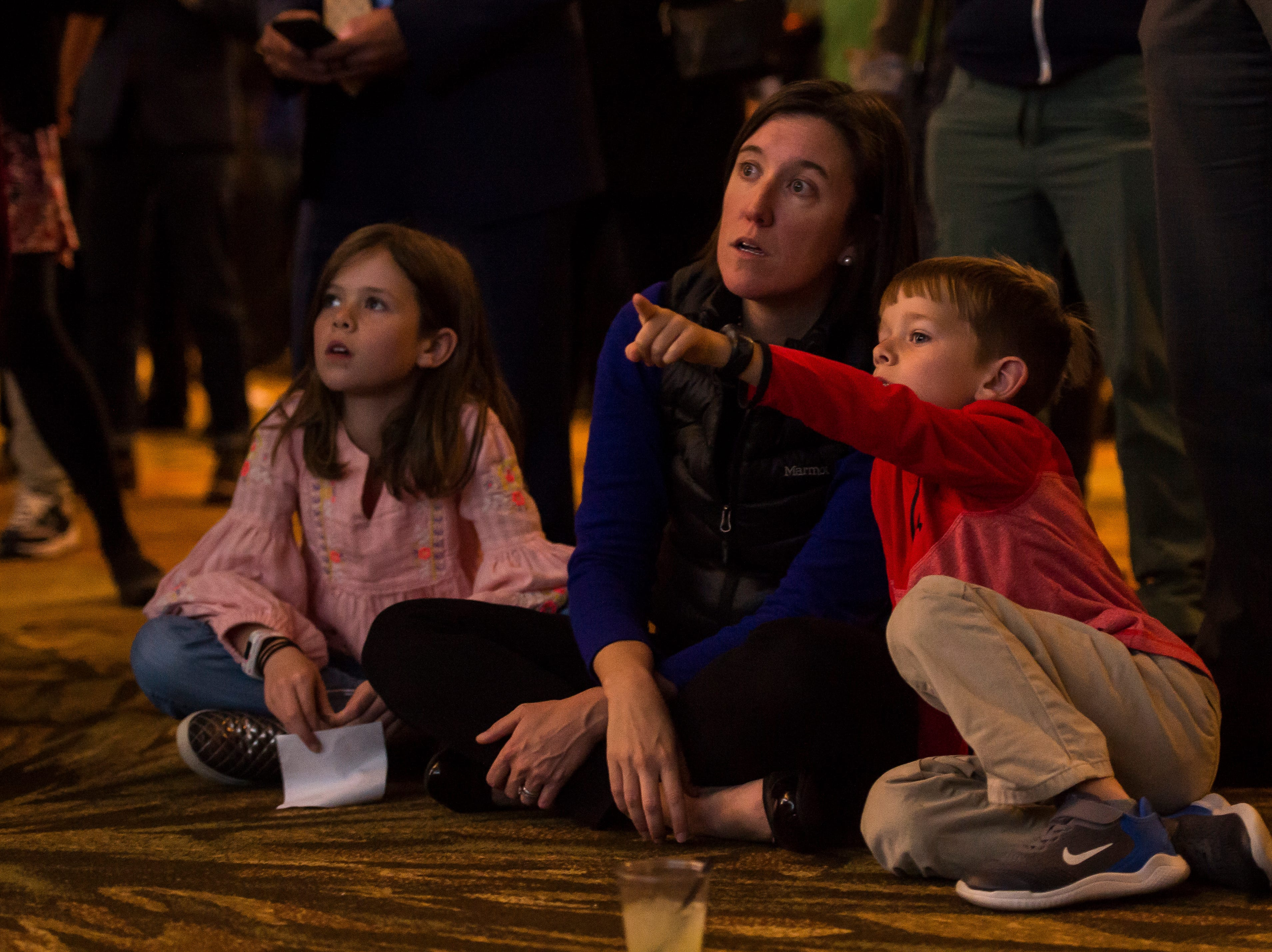 Cody Belly watches election results on a projection screen with her daughter Liza, 8, and son Cooper, 6, at Democratic candidate for Colorado governor Jared Polis' election watch party on Tuesday, Nov. 6, 2018, at the Westin Denver Downtown hotel in Denver, Colo.