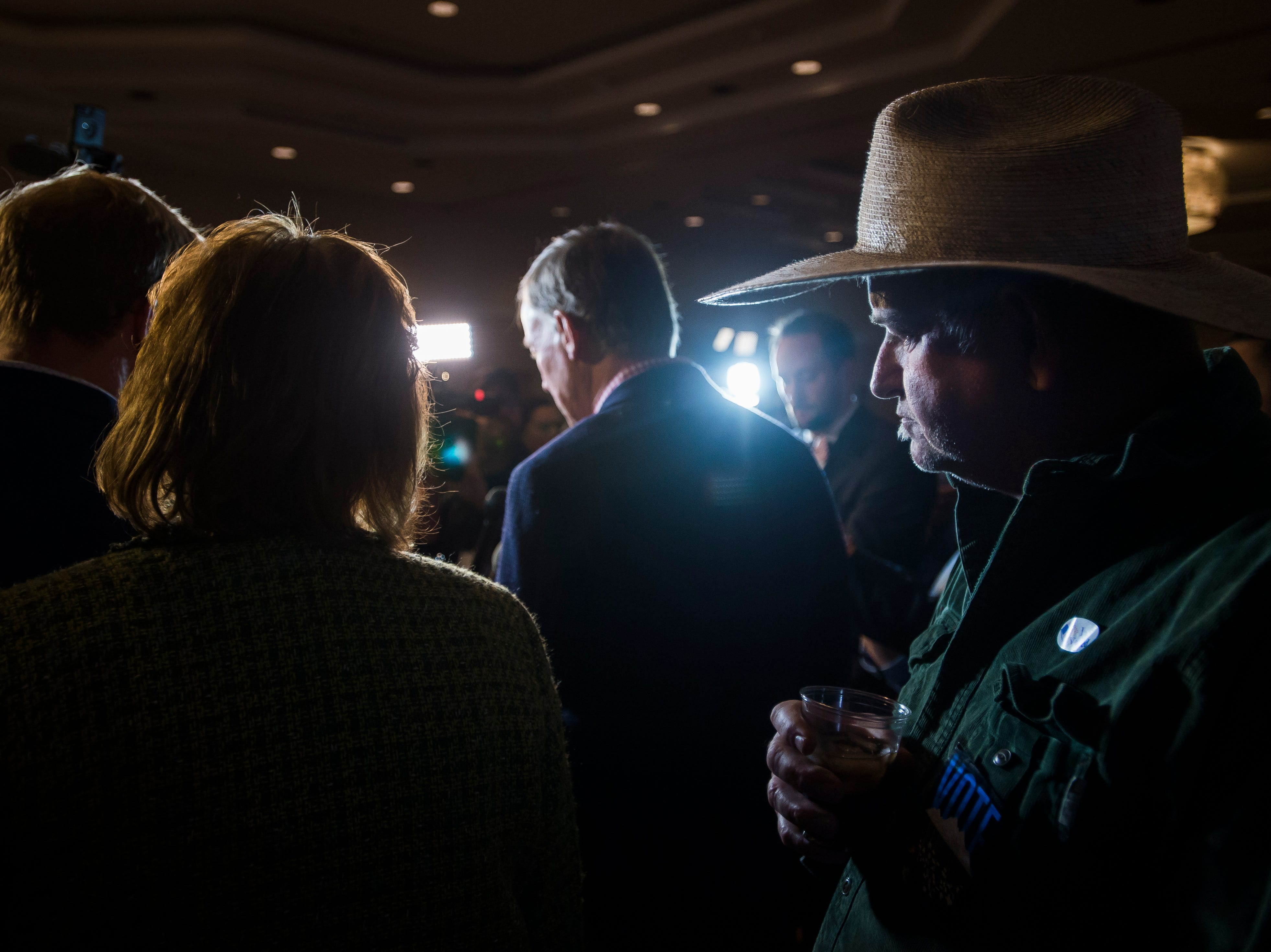 Fort Collins resident Lan Grant, right, listens to Colorado Governor John Hickenlooper as he talks with members of the media before an election watch party for Democratic candidate for Colorado governor Jared Polis on Tuesday, Nov. 6, 2018, at the Westin Denver Downtown hotel in Denver, Colo.