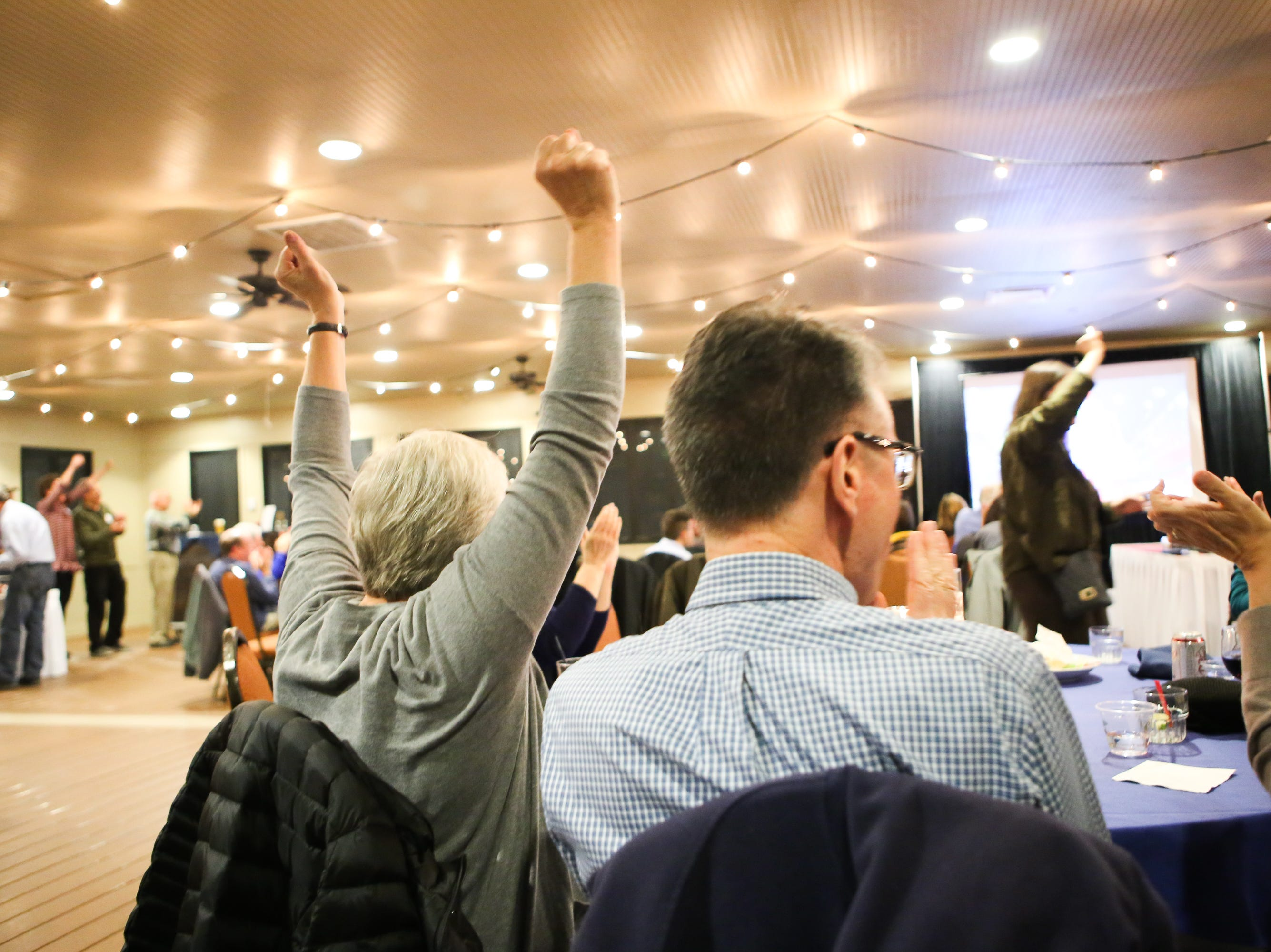 Linda Akey cheers with other attendees of the Democratic watch party at the Fort Collins Marriott after votes roll in favoring the Democrats.