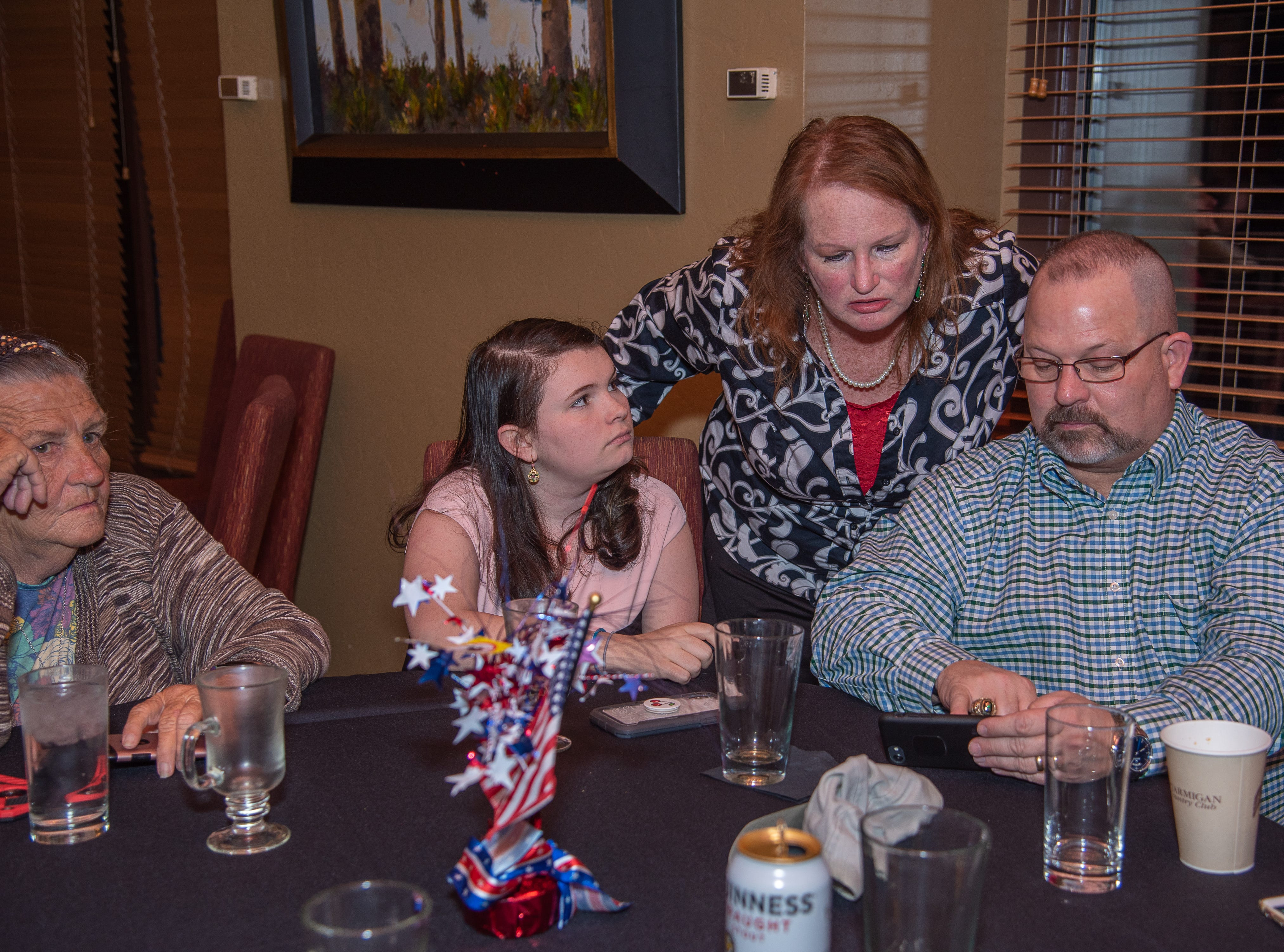 GOP assessor candidate Alexis Smith looks at early election results with family members at an election watch party on Tuesday, November 6, 2018, at Ptarmigan Country Club in Fort Collins, Colo.