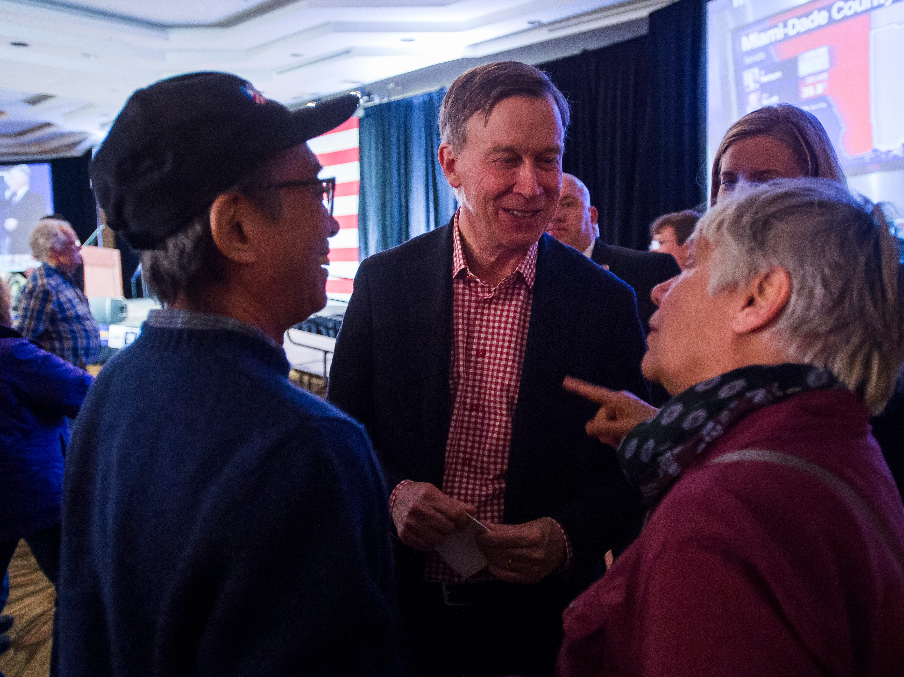 Colorado Governor John Hickenlooper talks with friends Alan O'Hashi and Diana Helzer before an election watch party for Democratic candidate for Colorado governor Jared Polis on Tuesday, Nov. 6, 2018, at the Westin Denver Downtown hotel in Denver, Colo.
