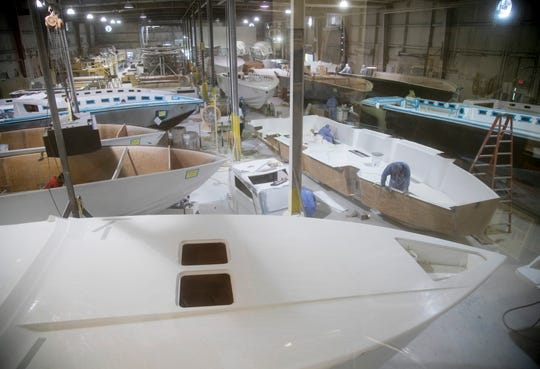 Employees at Nor-Tech Hi-Performance Boats work on the hulls of their custom boats on Wednesday, November 7, 2018, in North Fort Myers.