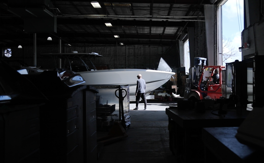 A nearly complete boat is brought into the warehouse at Nor-Tech Hi-Performance Boats in North Fort Myers on Wednesday.