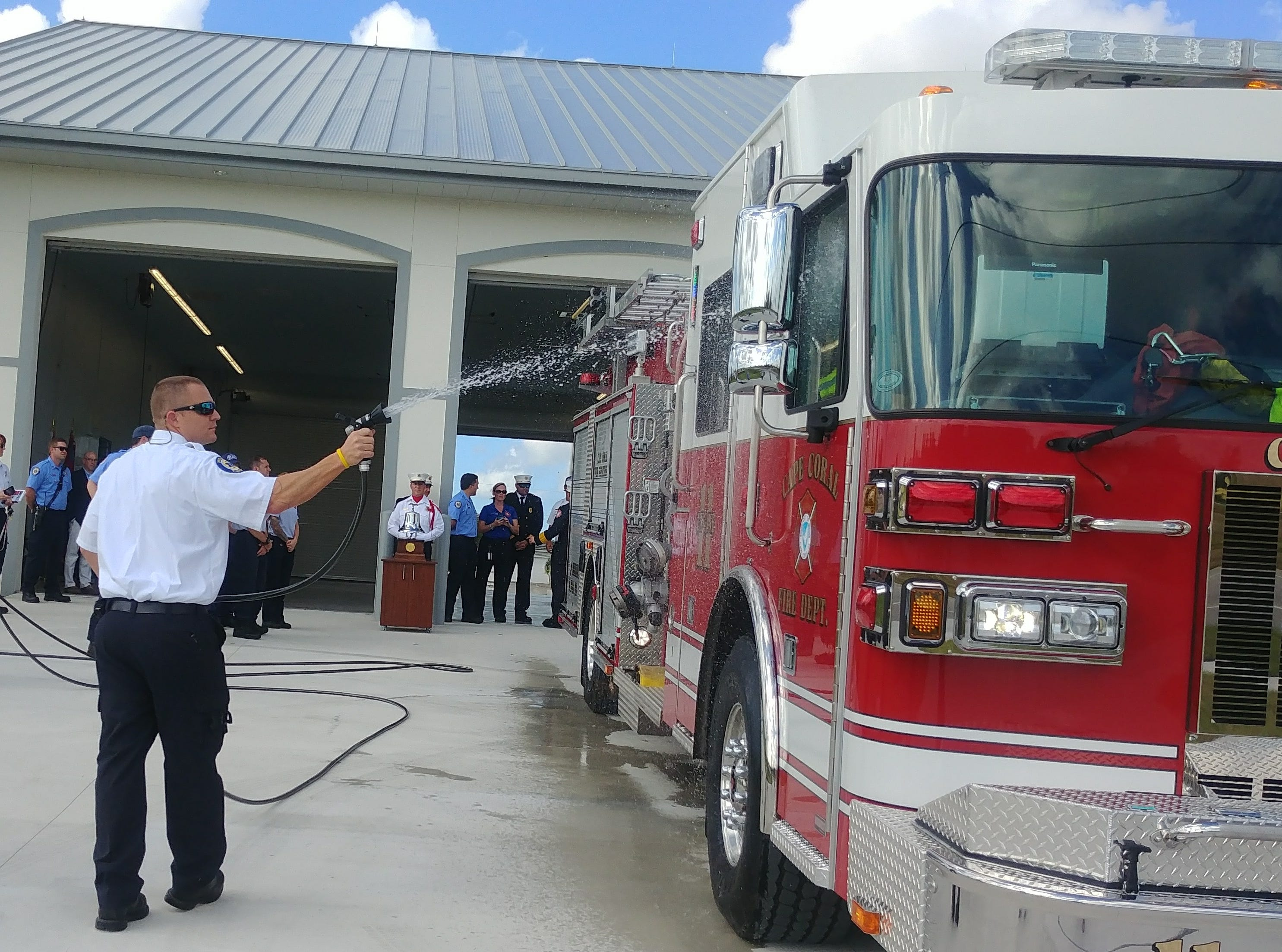 """A Cape Coral firefighter washes down the new Engine 11 during """"homing"""" ceremony for the truck at the new Station 11."""
