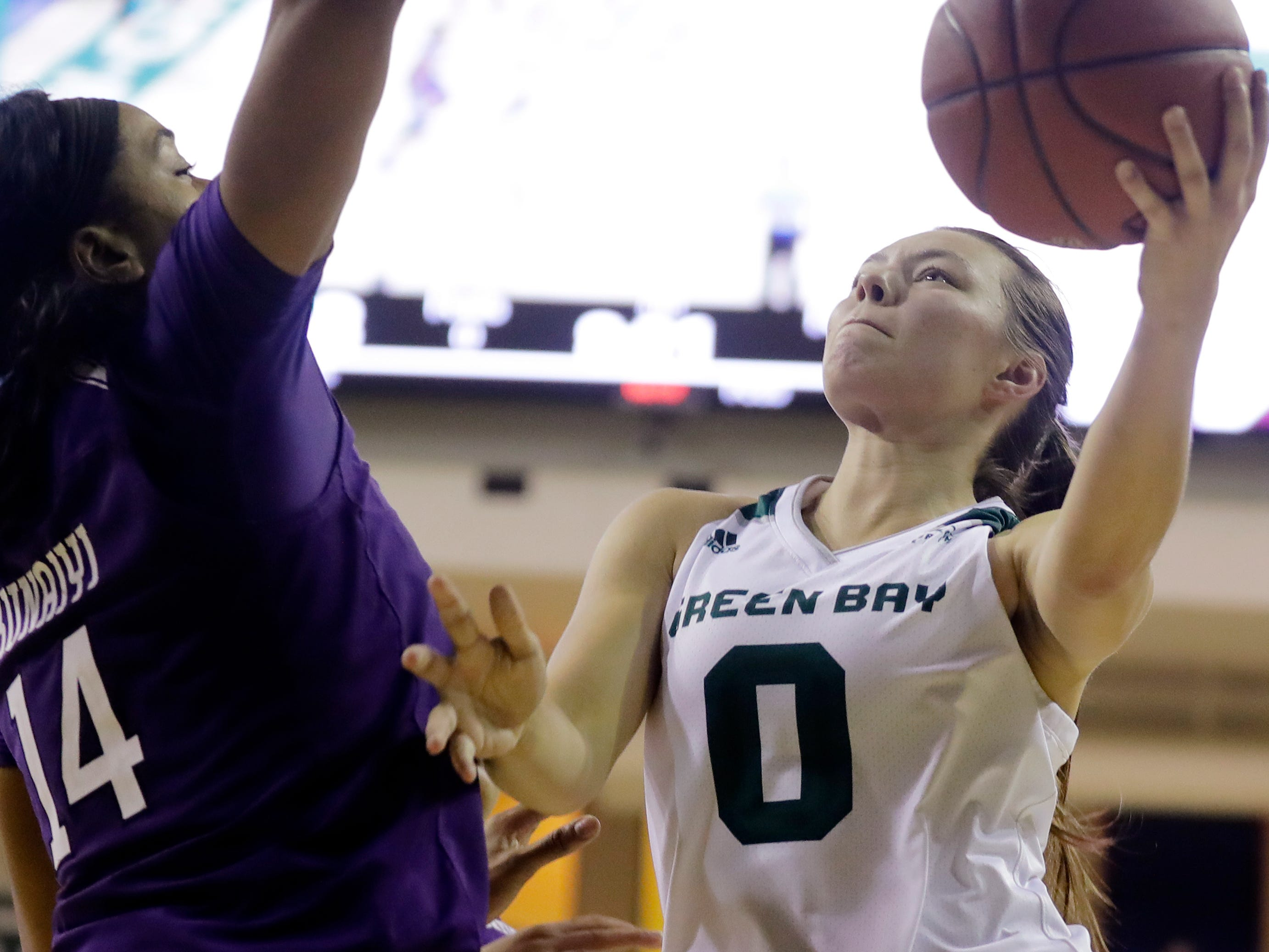 Green Bay Phoenix guard Hailey Oskey (0) drives to the basket against Northwestern Wildcats forward Pallas Kunaiyi-Akpanah (14) in a women's NCAA basketball game at the Kress Center on Tuesday, November 6, 2018 in Green Bay, Wis.