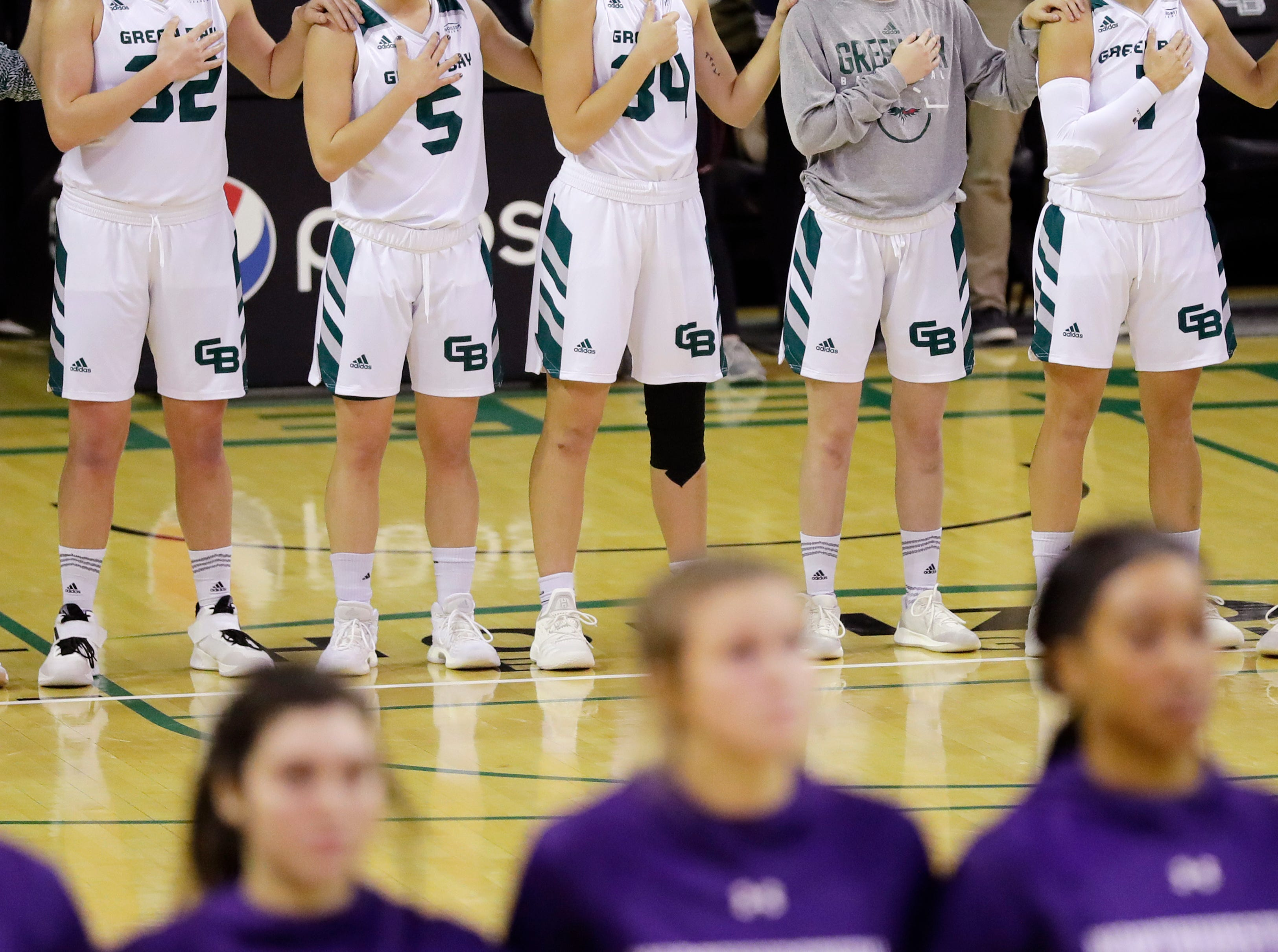 Green Bay Phoenix players lineup for the national anthem before facing the Northwestern Wildcats in a women's NCAA basketball game at the Kress Center on Tuesday, November 6, 2018 in Green Bay, Wis.