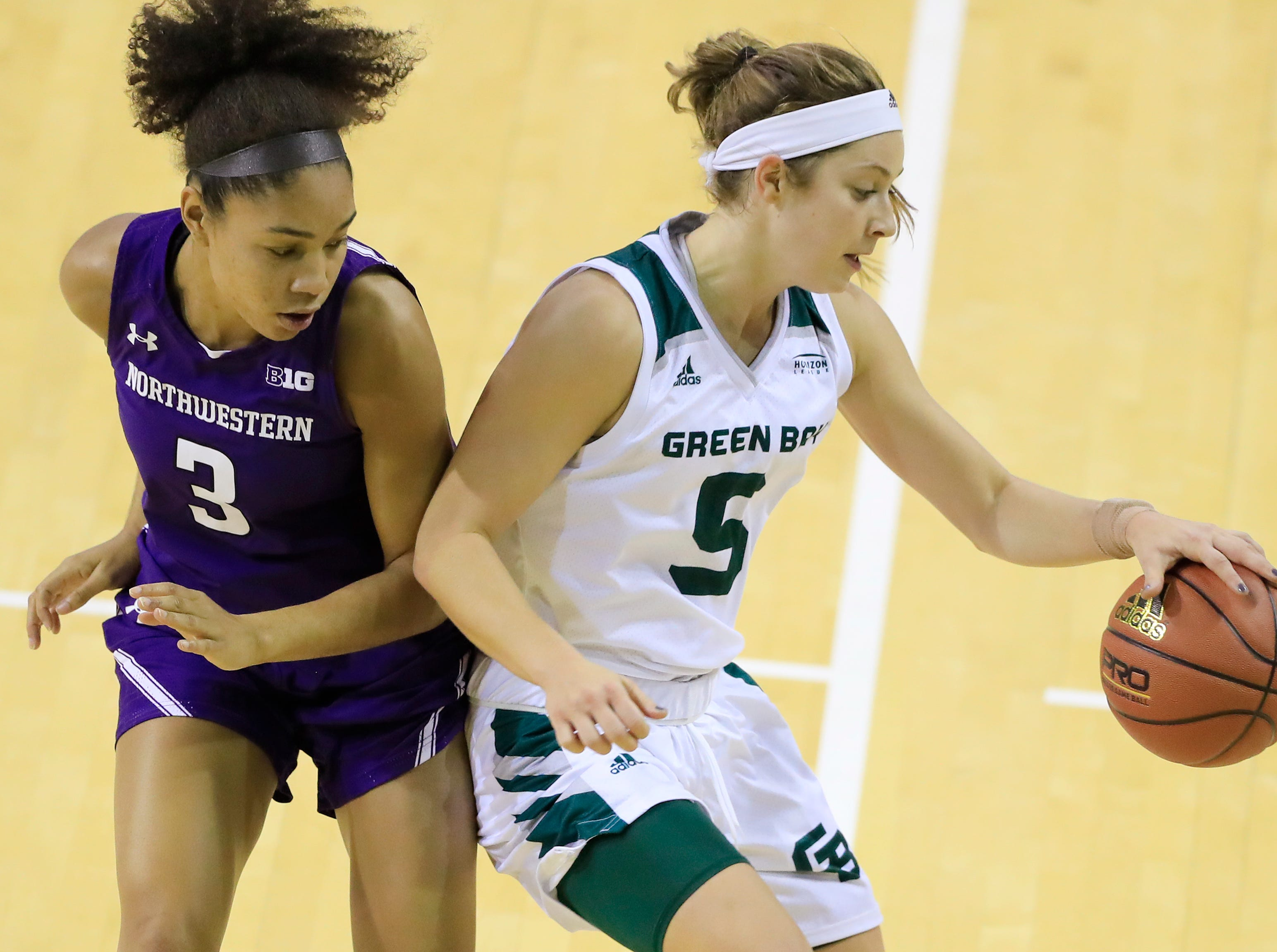 Green Bay Phoenix guard Laken James (5) spins away from Northwestern Wildcats guard Sydney Wood (3) in a women's NCAA basketball game at the Kress Center on Tuesday, November 6, 2018 in Green Bay, Wis.