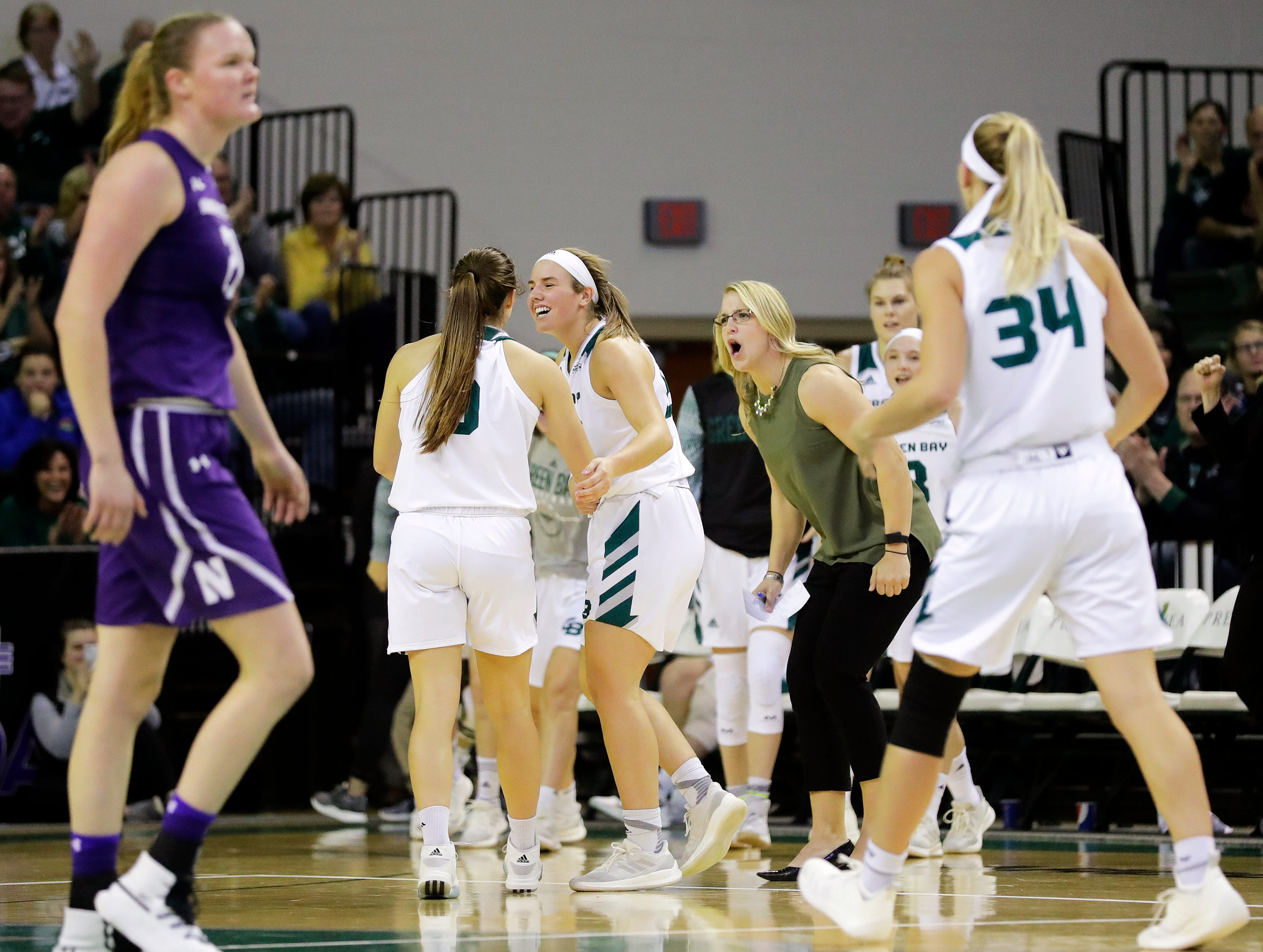 Green Bay Phoenix players celebrate with Green Bay Phoenix guard Hailey Oskey (0) after she hit a 3-pointer against the Northwestern Wildcats in a women's NCAA basketball game at the Kress Center on Tuesday, November 6, 2018 in Green Bay, Wis.