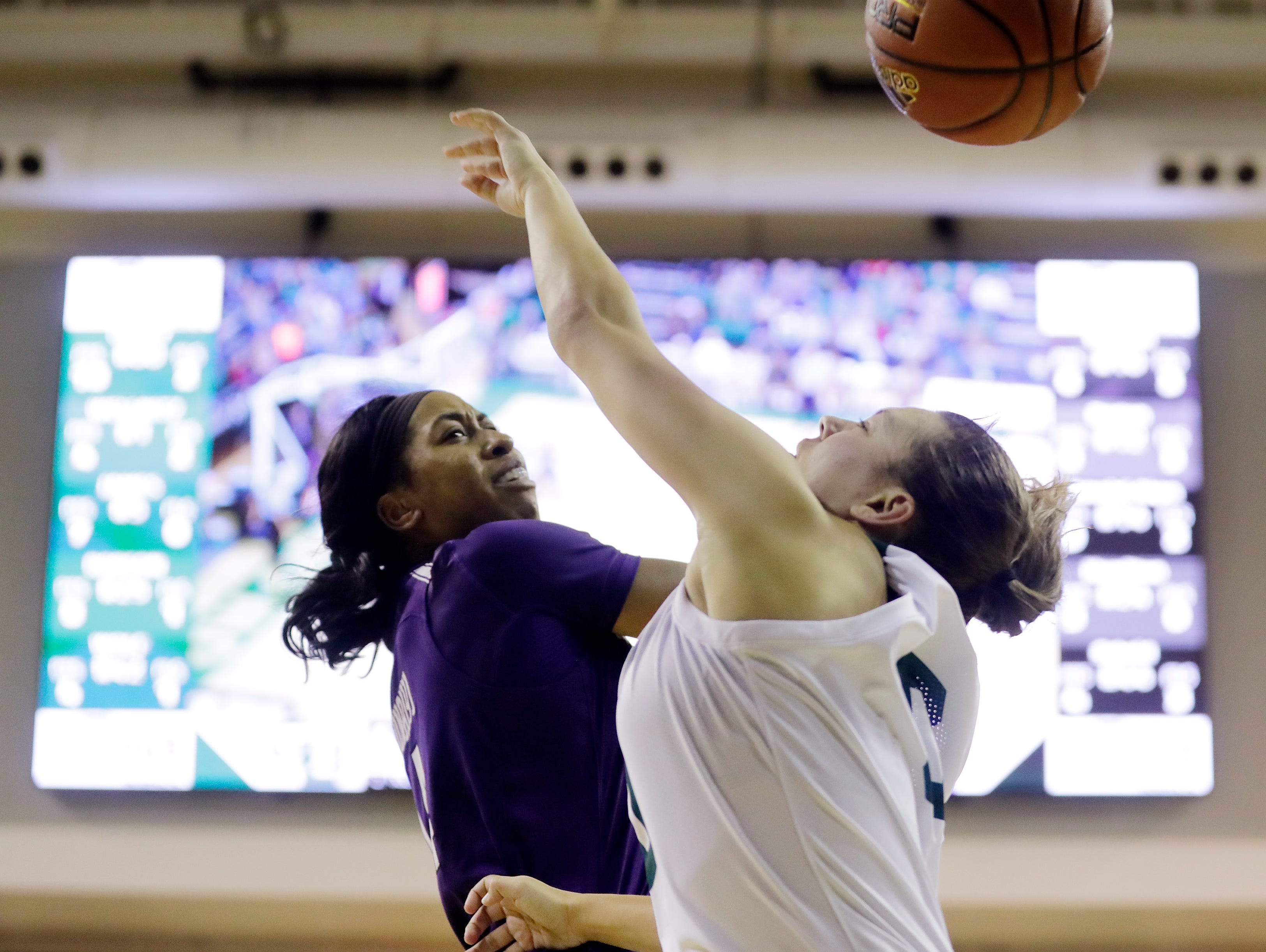 Green Bay Phoenix guard Hailey Oskey (0) has a shot blocked by Northwestern Wildcats forward Pallas Kunaiyi-Akpanah (14) in a women's NCAA basketball game at the Kress Center on Tuesday, November 6, 2018 in Green Bay, Wis.