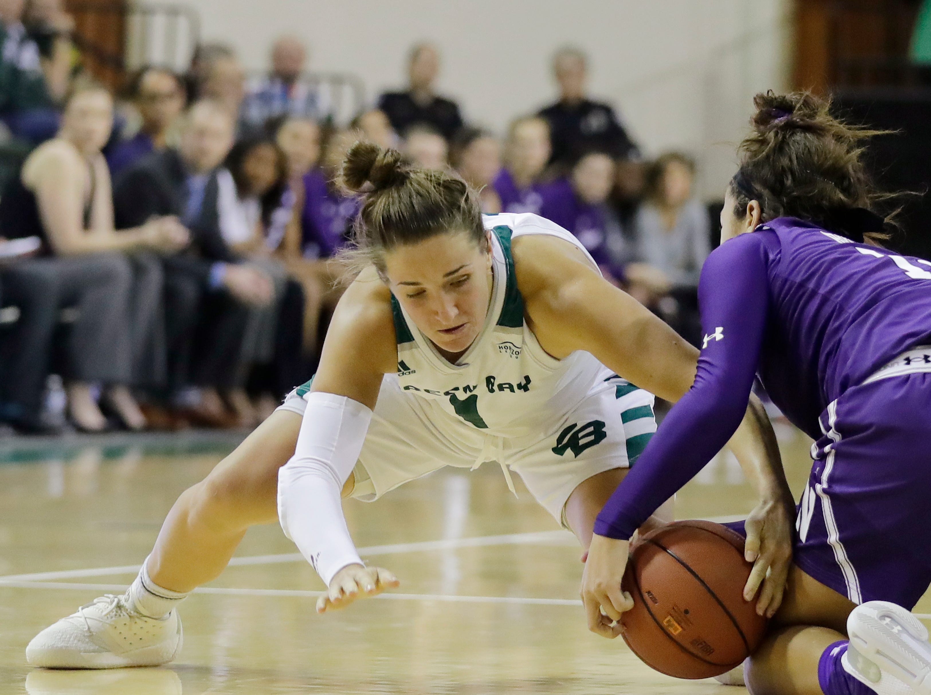 Green Bay Phoenix guard Jen Wellnitz (1) fights for a loose ball against Northwestern Wildcats guard Veronica Burton (12) in a women's NCAA basketball game at the Kress Center on Tuesday, November 6, 2018 in Green Bay, Wis.