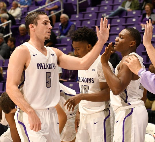 Teammates high five Furman's Andrew Brown (5) after his game against Bob Jones Tuesday, November 6, 2018, at Timmons Arena.