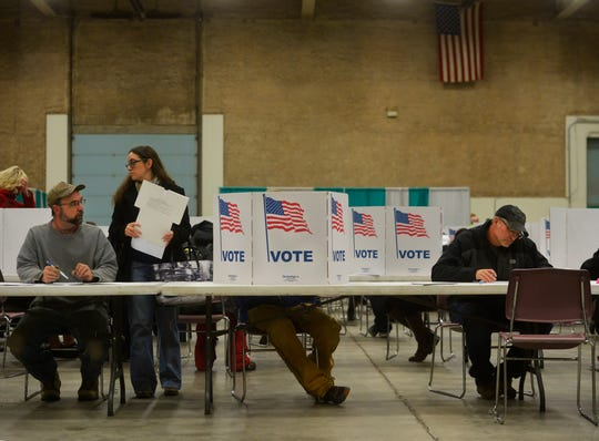 Voters cast their ballots at Exhibition Hall on Tuesday evening.
