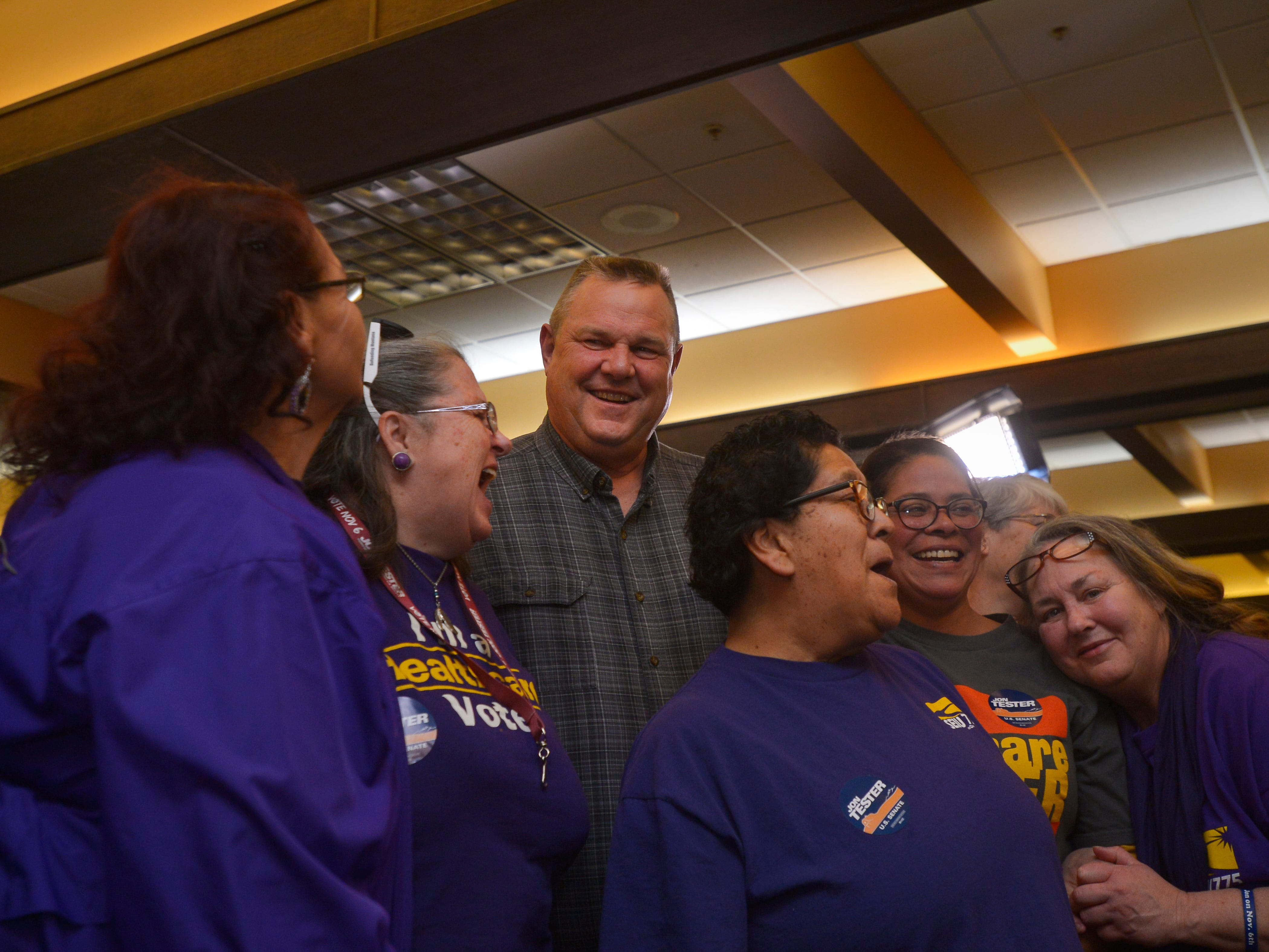 Senator Jon Tester poses for a photo with members of the Service Employees International Union, which represents care givers around the state, Tuesday night during his election night party at the Holiday Inn in Great Falls.