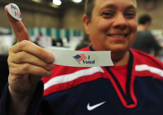 """Kelly Quick proudly holds up her """"I voted"""" sticker after casting her ballot at Exhibition Hall on Tuesday."""